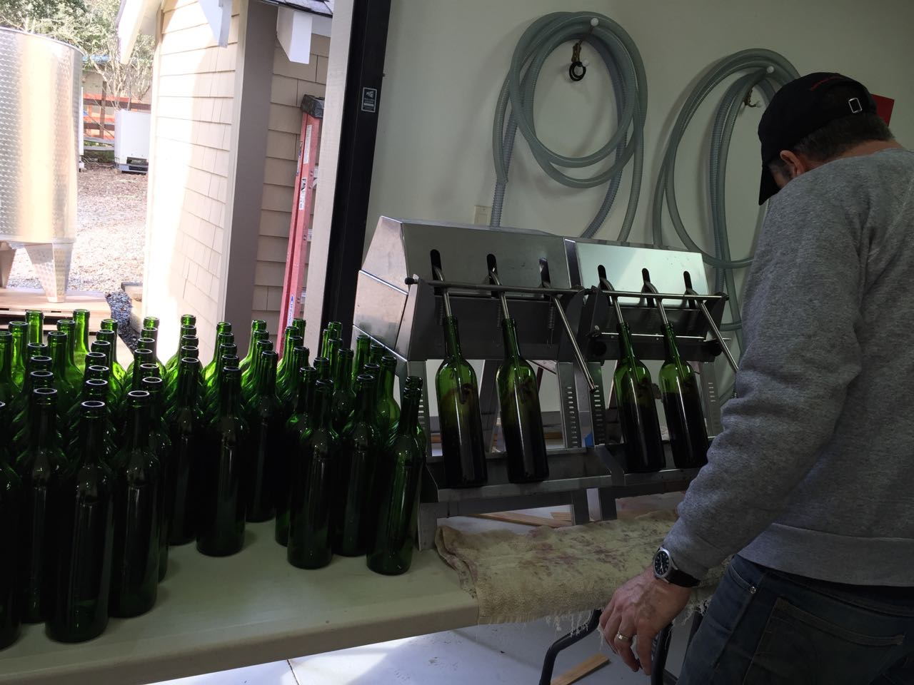 New bottles are placed in filler(wine is fed into filler by gravity with no pumping)