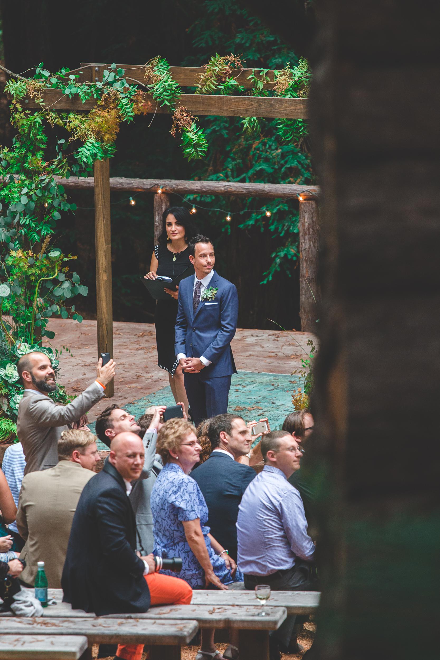 groom watching bride walk down aisle