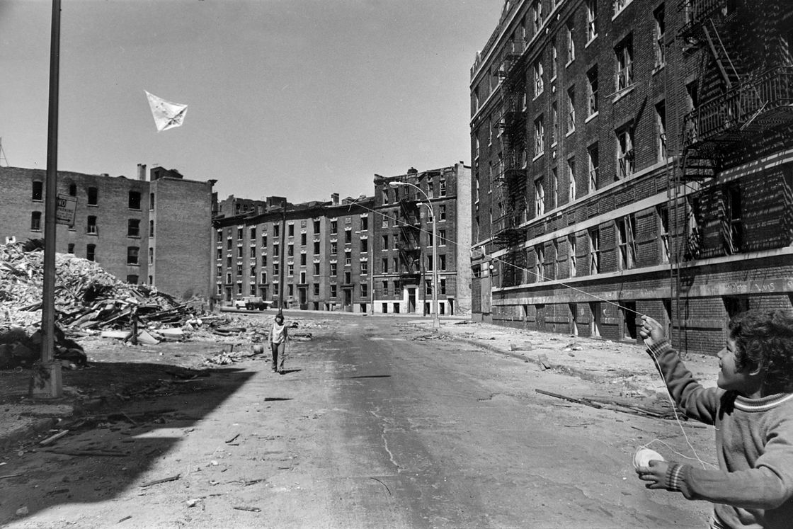 Youths fly a kite in a street bordered with firegutted buildings in the South Bronx section of New York City in June, 1977. The Carter Administration has agreed to revive urban renewal projects in an effort to revive the neighborhood. | AP Images