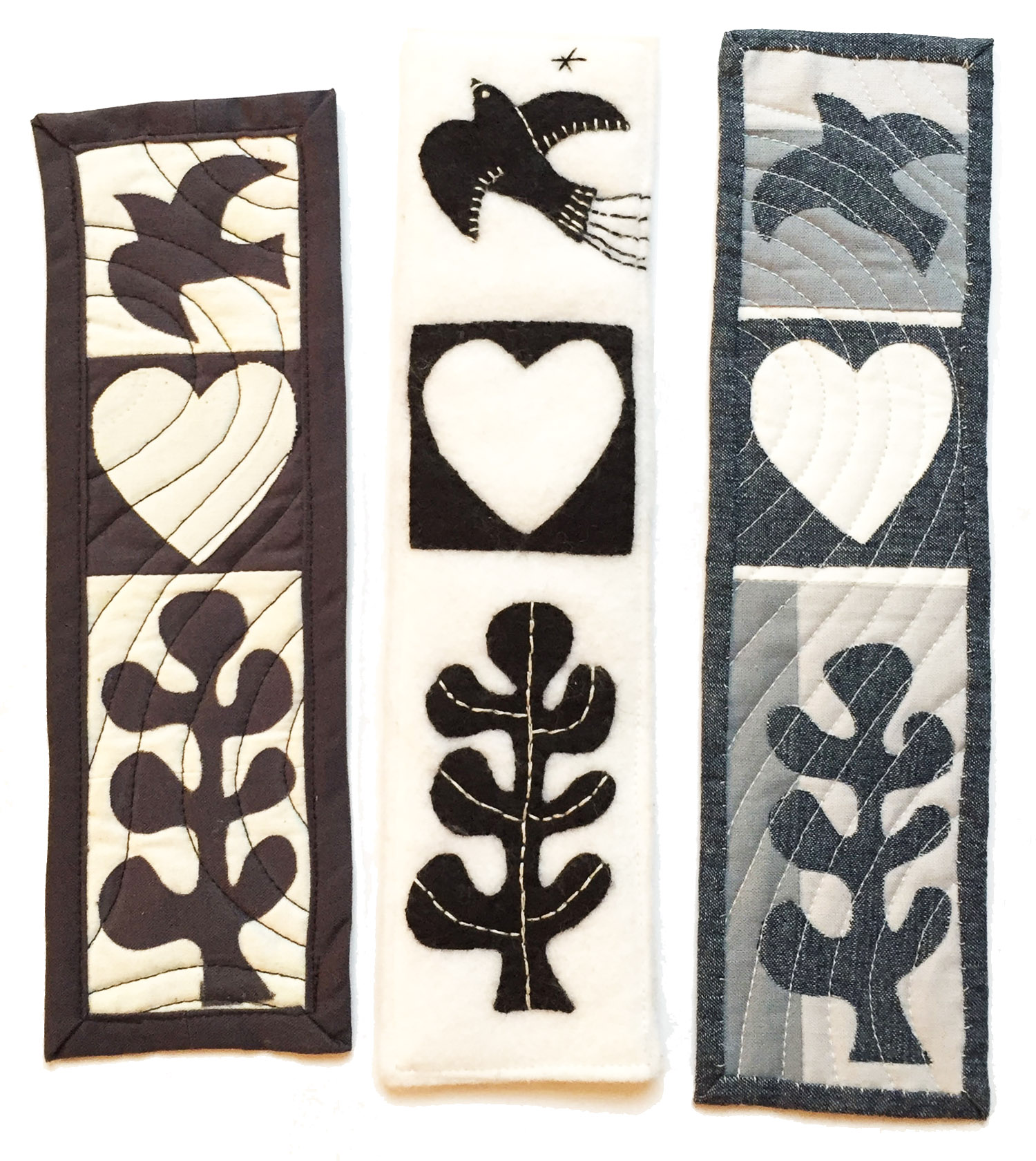The middle bookmark is made with wool felt and embroidery. The bookmark on the right is lower in contrast due to the addition of two shades of gray.