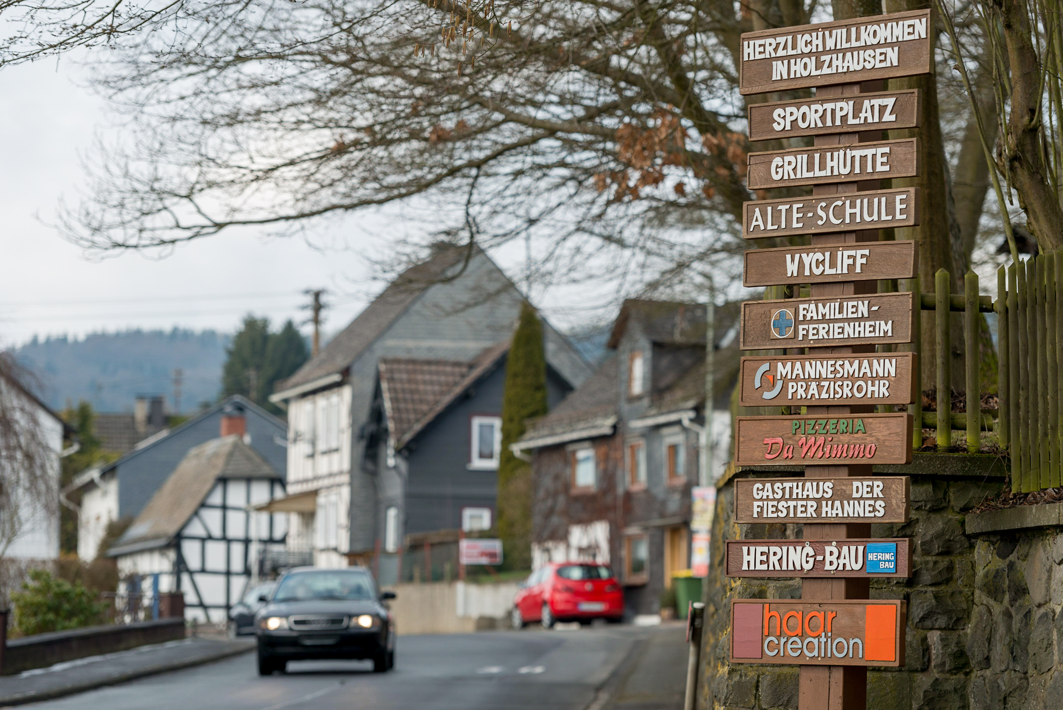 Information signs located along one of the main entrances to Holzhausen, Germany, tell drivers about the various firms and organizations located in the village. Typical half-timbered and slate-sided homes are visible in the background.