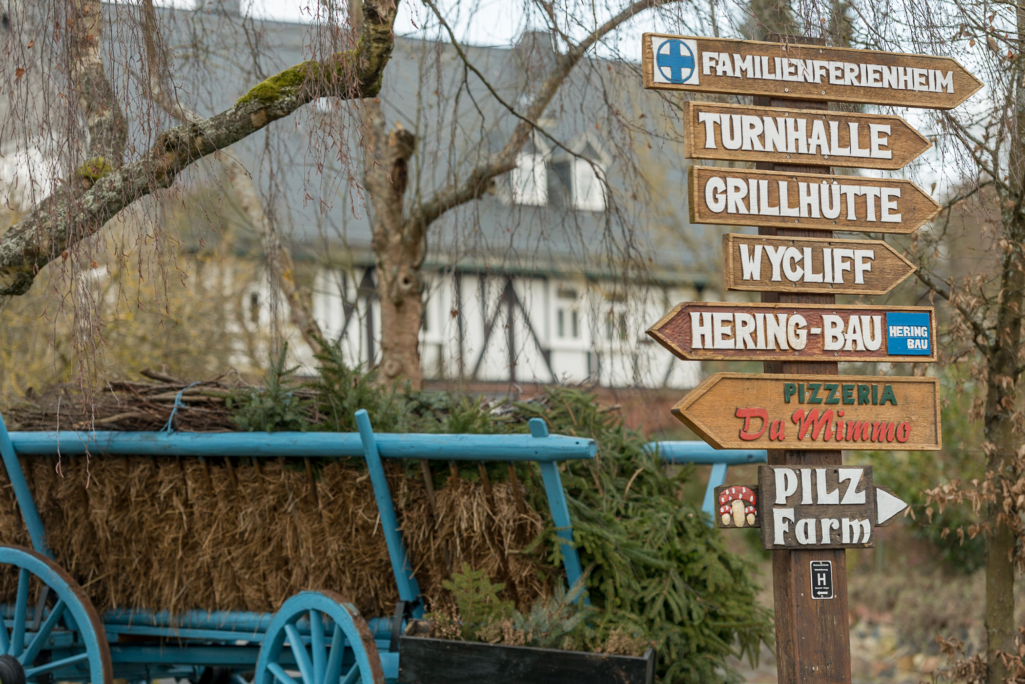 Information signs in the center of Holzhausen, Germany, tell drivers the locations of various firms and organizations located in the village. Typical half-timbered and slate-shingled homes are visible in the background.