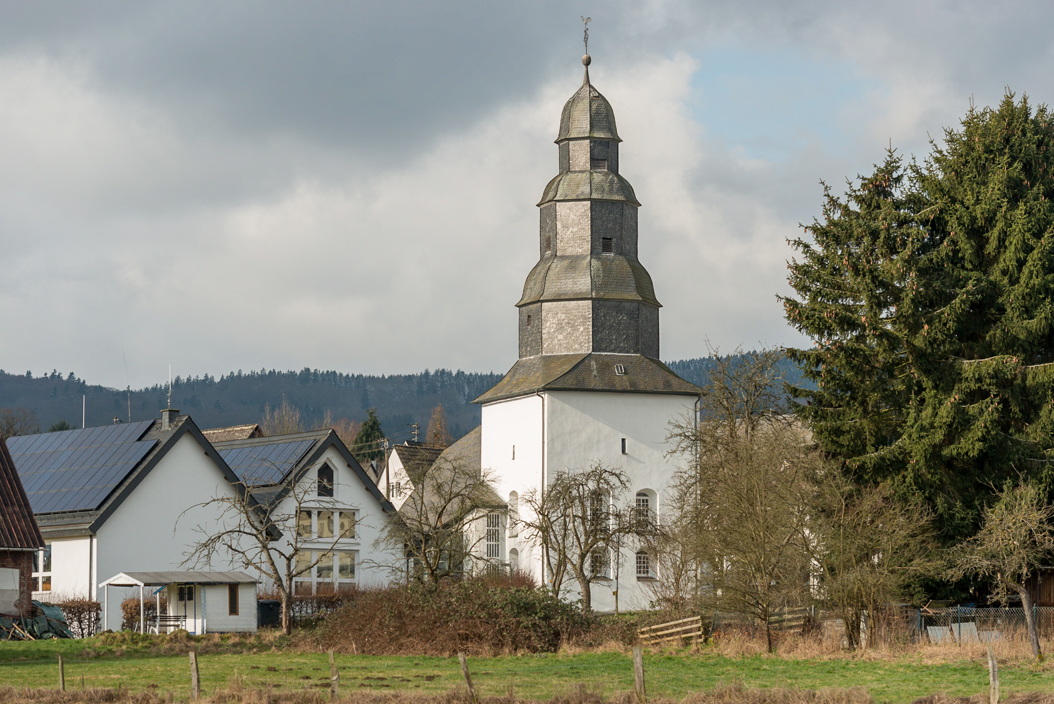 One of Holzhausen's most unique and recognizable structures, the state church's octagonal, slate-shingled steeple rises in the heart of the old town center, nestled between additonal church buildings and a large evergreen tree.