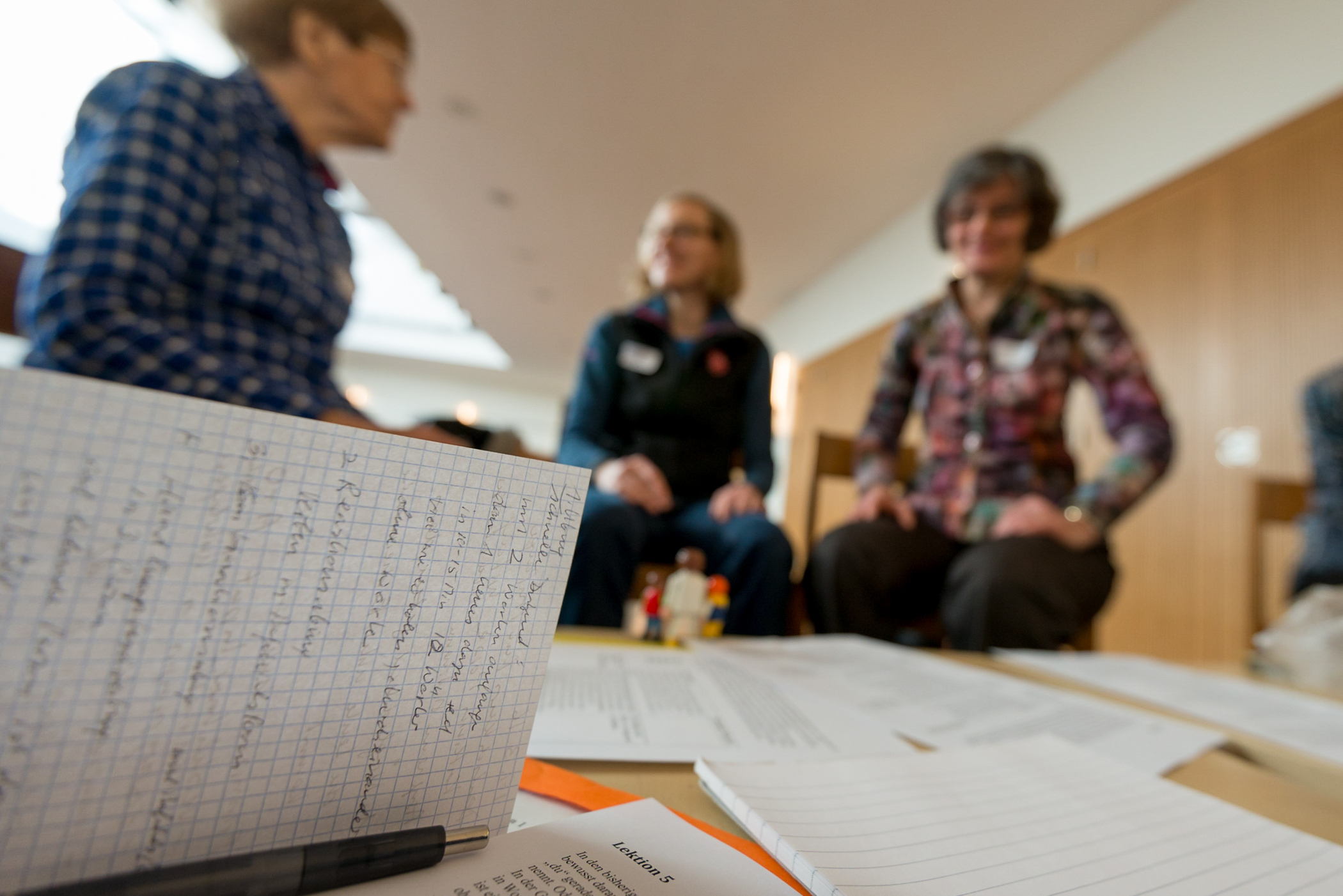 Participants' notes and pre-printed course materials rest on a table as they develop a sample language-learning exercise during the German for Refugees course offered at Gellertkirche, in Basel, Switzerland. The German for Refugees course is a train-the-trainer course designed to equip Swiss to teach their language to recently arriving refugees.