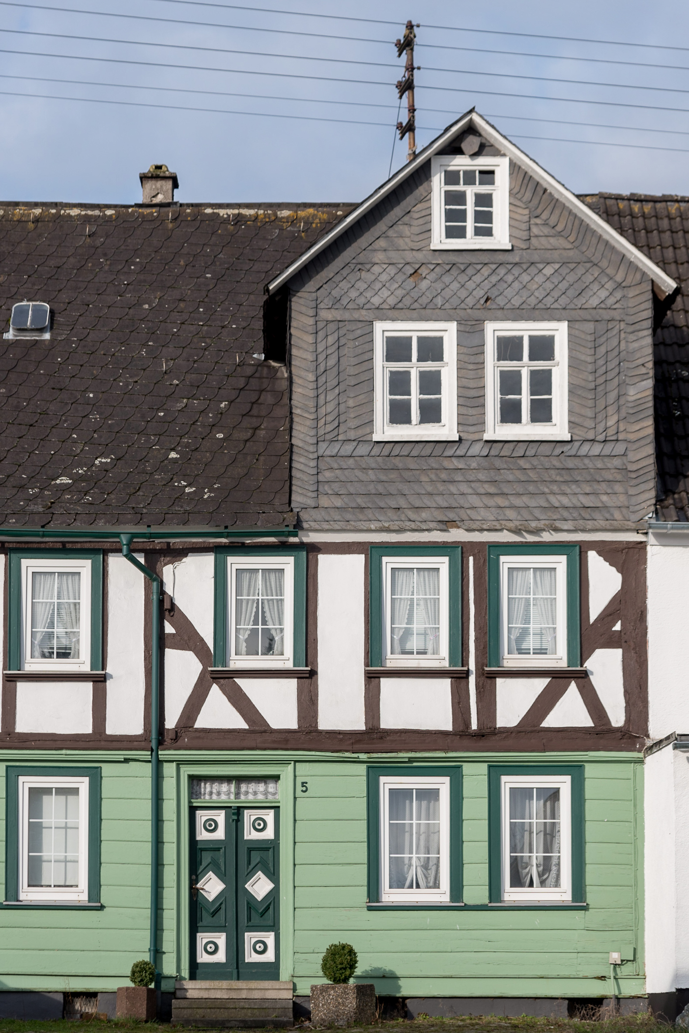 This German home in Holzhausen, Germany, features a multi-story, half-timbered design, as well as slate shingle siding and brightly-painted window frames and door.
