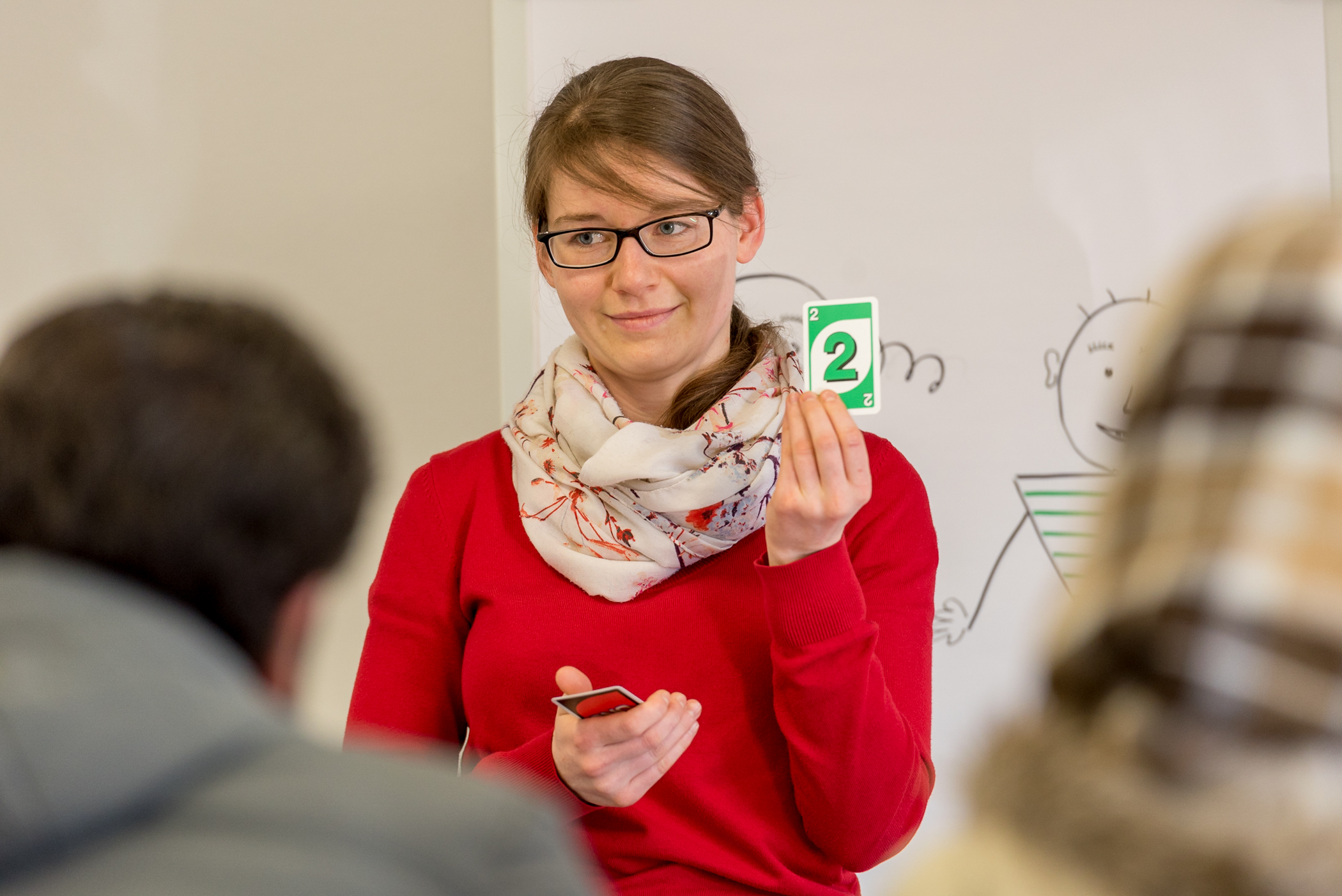 Helene Celiscev presents her sample lesson, using cards from a common game, to a couple of recently-arrived refugees from West Asia. Helene's lesson is meant to teach the words for colors and numbers up to 10. Helene's mother tongue is German [deu]. The German for Refugees course is a train-the-trainer course designed to equip Germans to teach their language to recently arriving refugees.