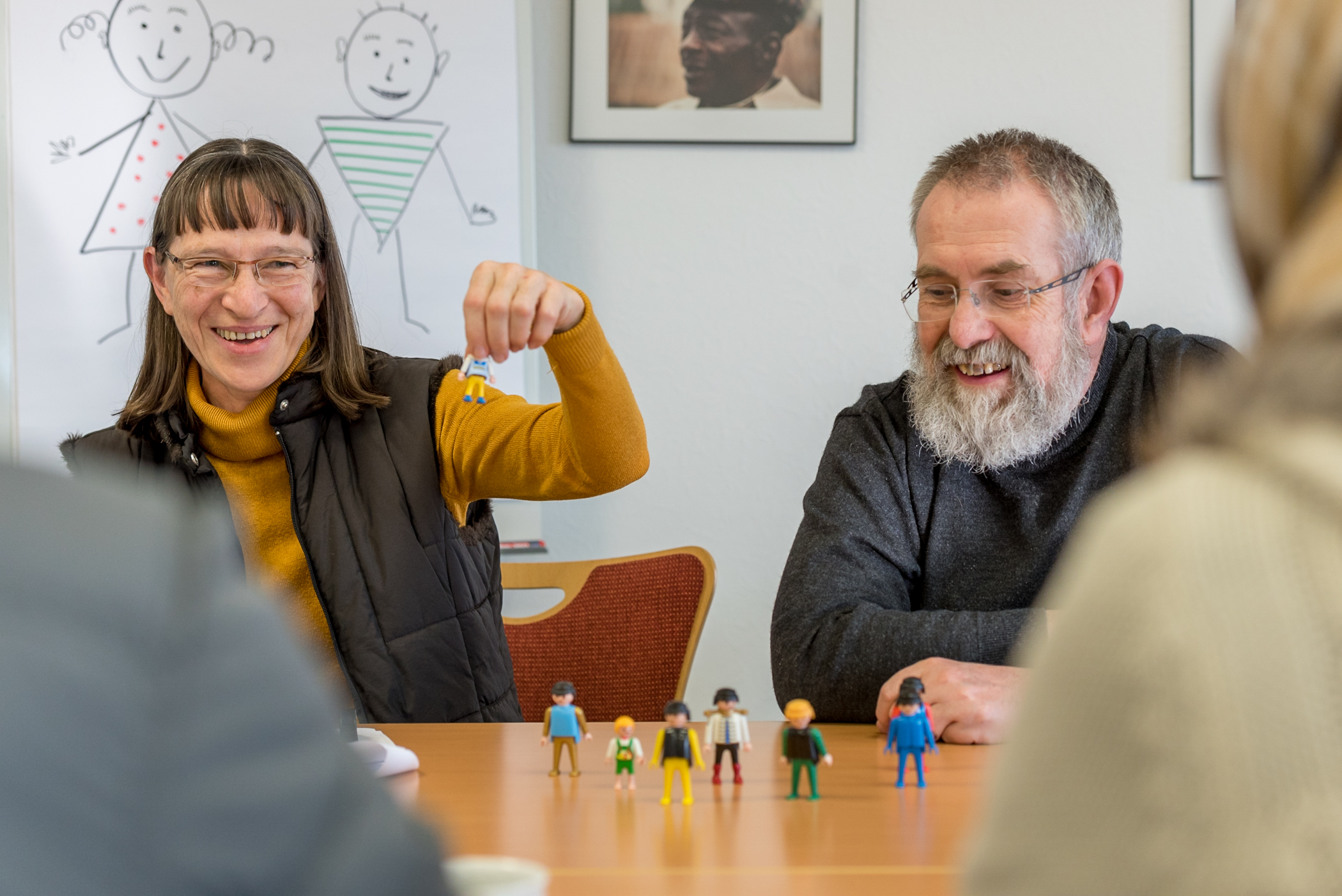 Dorothee and Eugen Müller present their sample lesson, using figures from a common toy line, to a couple of recently-arrived refugees from West Asia. The Müllers' lesson is meant to teach descriptive terms for people, like hair color, size, and gender.  Particpants are selecting the figures that match the descriptions they hear the Müllers say. Dorothee and Eugen's mother tongue is German [deu]. The German for Refugees course is a train-the-trainer course designed to equip Germans to teach their language to recently arriving refugees.