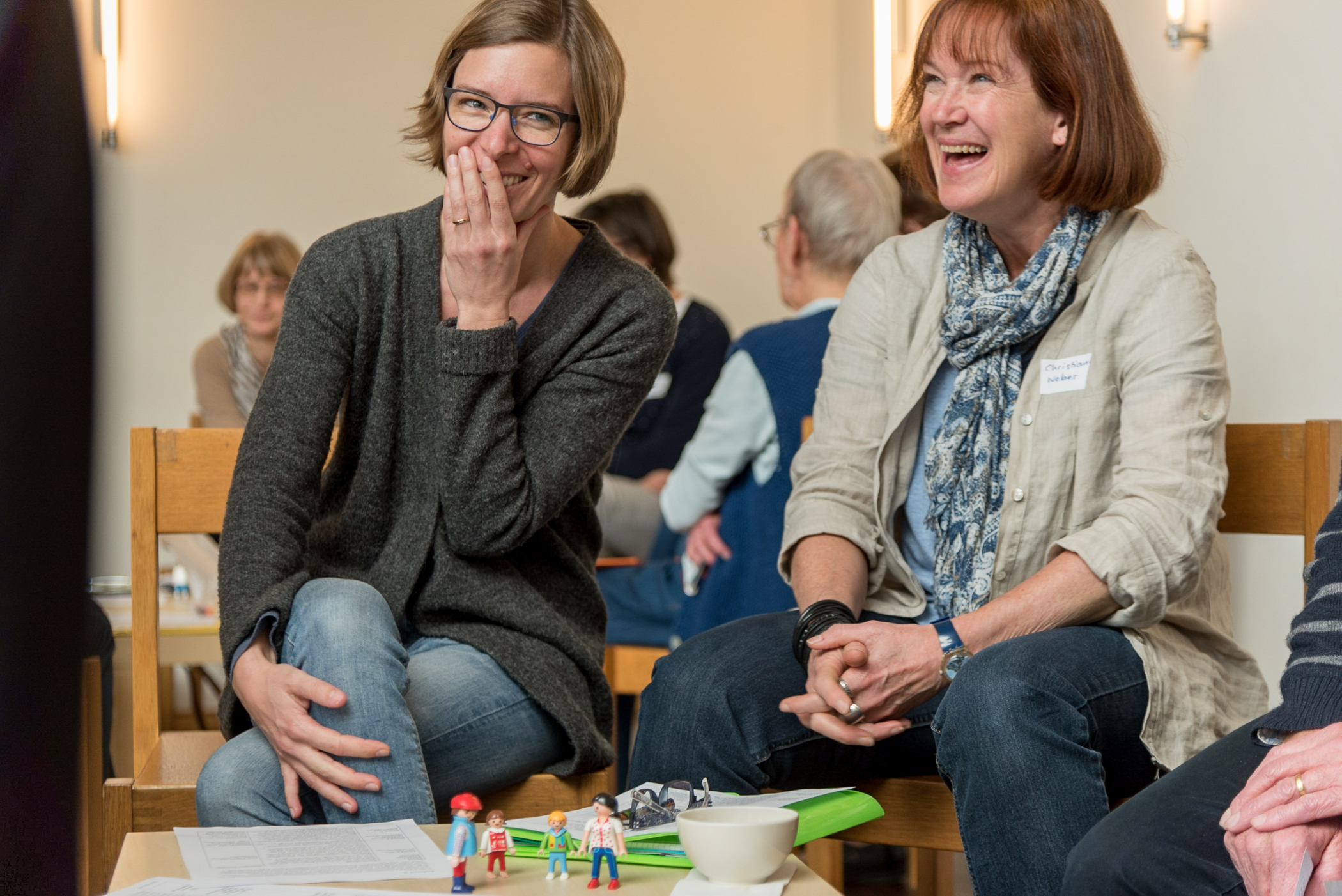 Mara Tobler and Chrisitane Weber laugh at their execution of the sample language-learning lesson they presented to their teammates in the German for Refugees course held at the Gellertkirche in Basel, Switzerland. Sample lessons are presented to larger groups of co-participants. Mara and Chrisitane's mother tongue is Swiss German [gsw]. The German for Refugees course is a train-the-trainer course designed to equip Swiss to teach their language to recently arriving refugees.