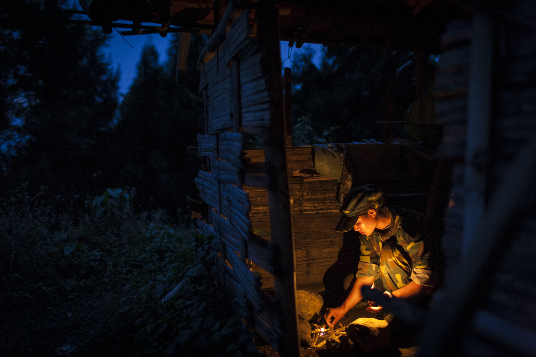 A woman learns to find food in the bush and cook over an open fire during the KIA's basic military training in Kachin State, Myanmar, May 13, 2013. As part of the training the soldiers spent two nights and three days sleeping in the jungle and walking for countless hours.