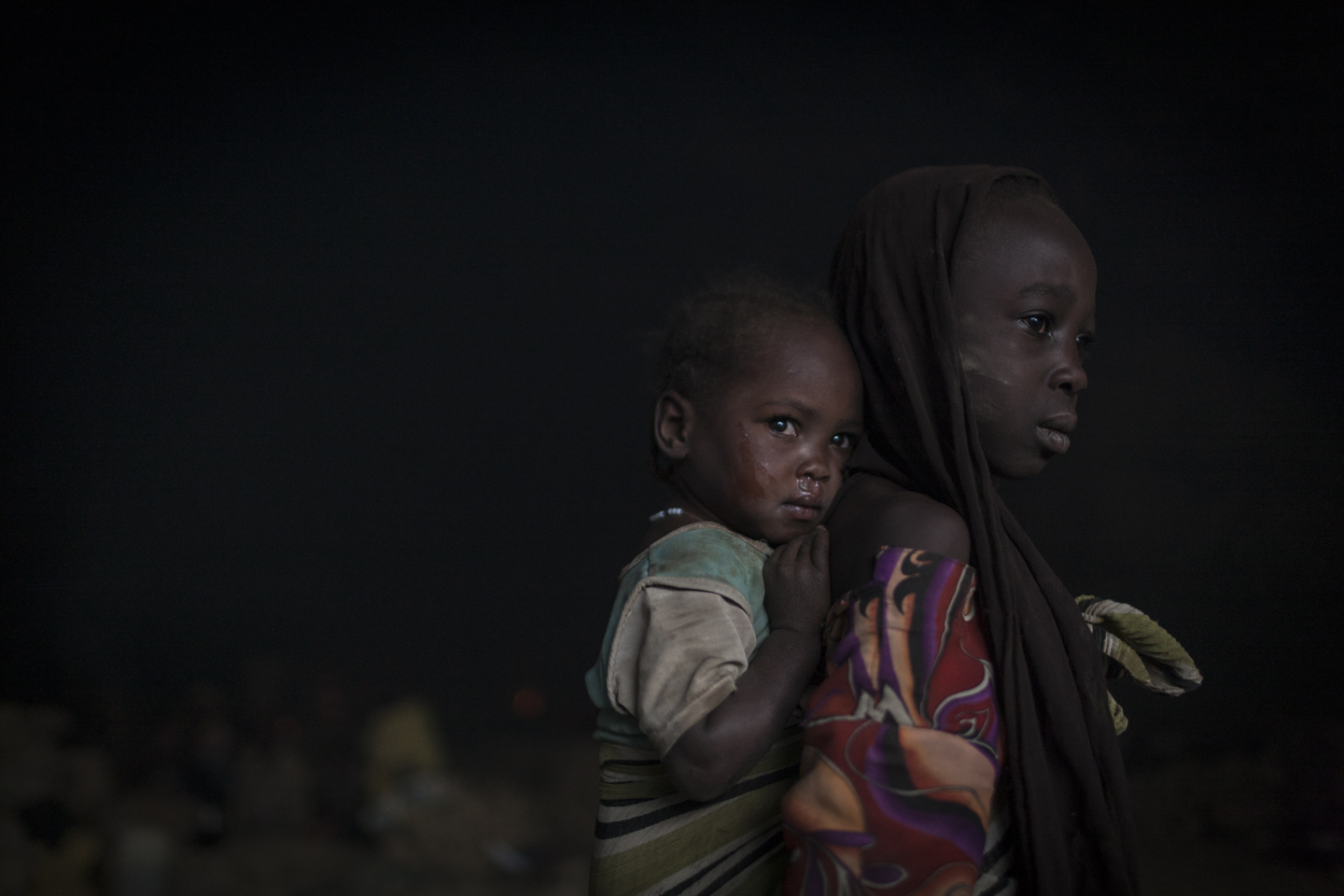 In the early morning sisters wake up in a cave where they sleep with hundreds of other people whose villages have been destroyed, or who are seeking shelter from the conintuned bombing ouside of Sarong in Central Darfur, Sudan, March 2, 2015.