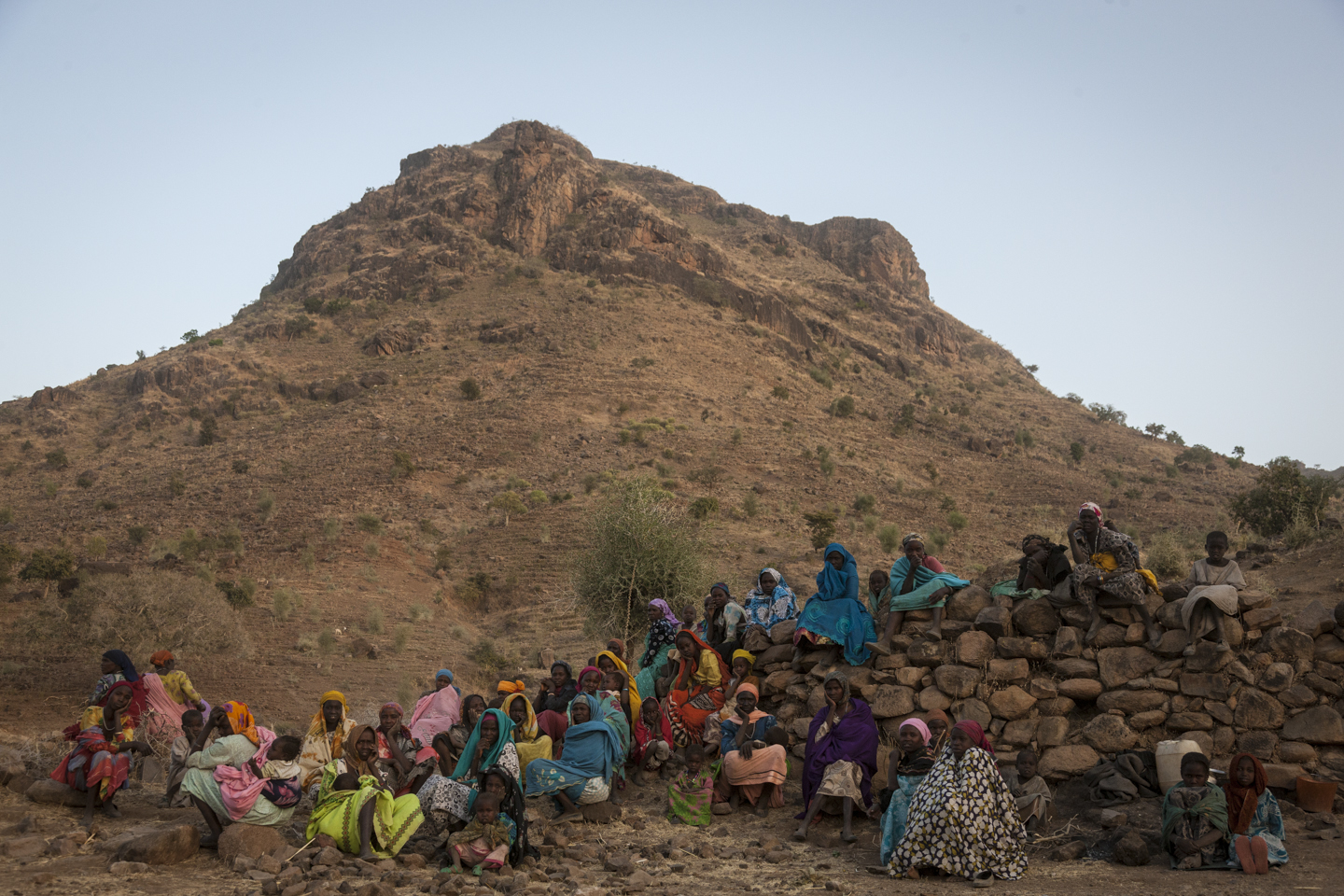 Women and children that have been displaced from the town of Golo after it was attacked by government forces and their allied militias, sit on a mountain top outside of Kome in Central Darfur, Sudan, February 28, 2015.