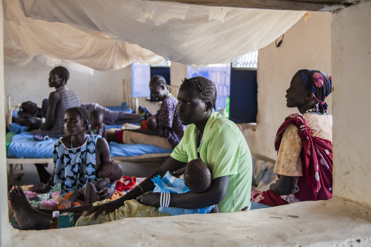 Women and their children rest in the inpatient ward of the Malualkon Primary Health Care Center in Malualkon, South Sudan, June 1st, 2012.
