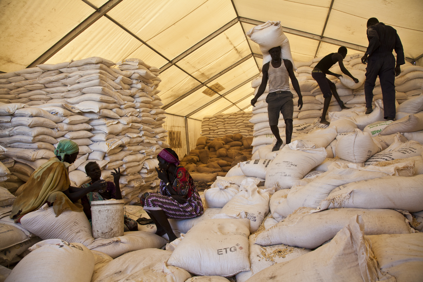 Men carry bags of food while women wait for their rations at the WFP food distribution site in Pibor, South Sudan, June 25th, 2012.