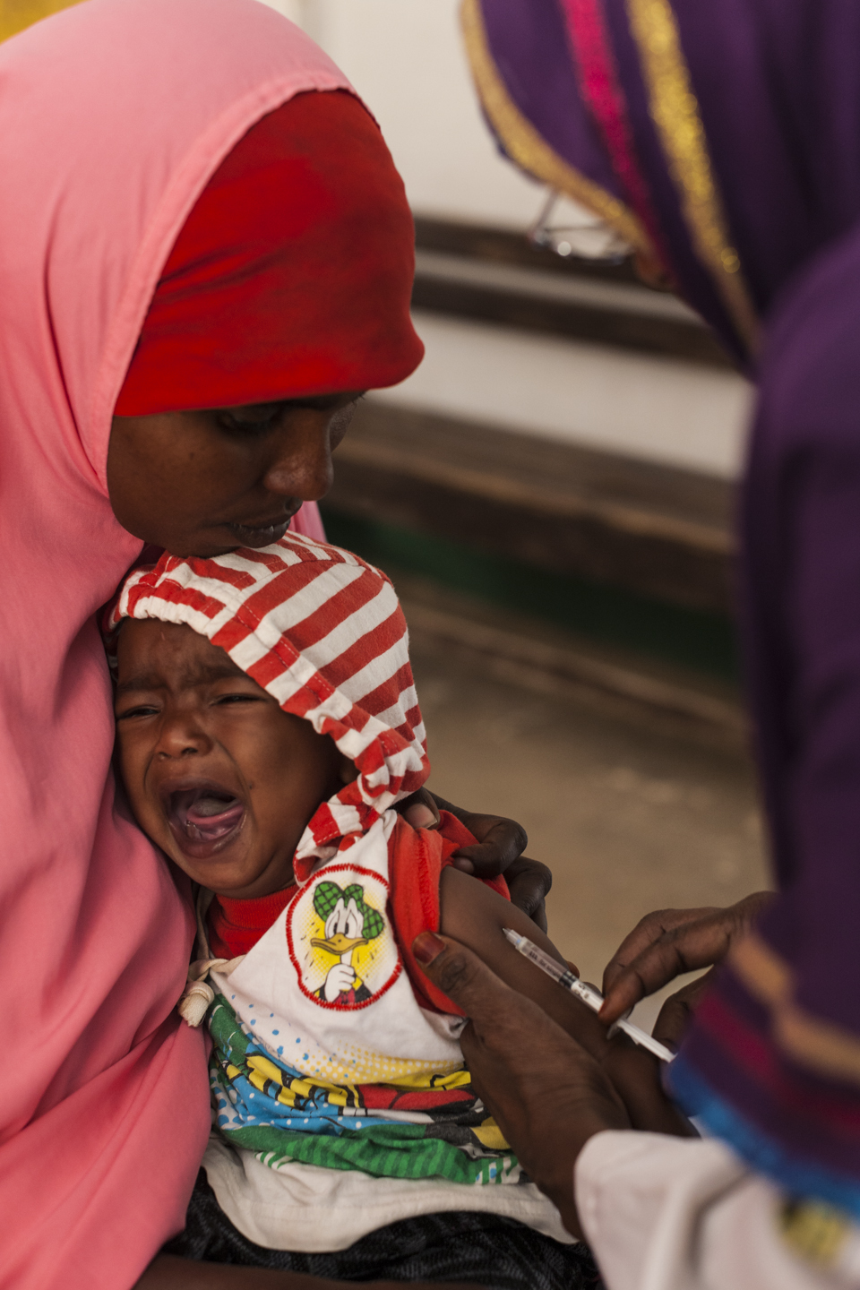Muuna sits with her four-month-old son Abdi while getting his vaccinations at the Central Burao Maternal and Child Health Center in Somaliland, November 12, 2014.