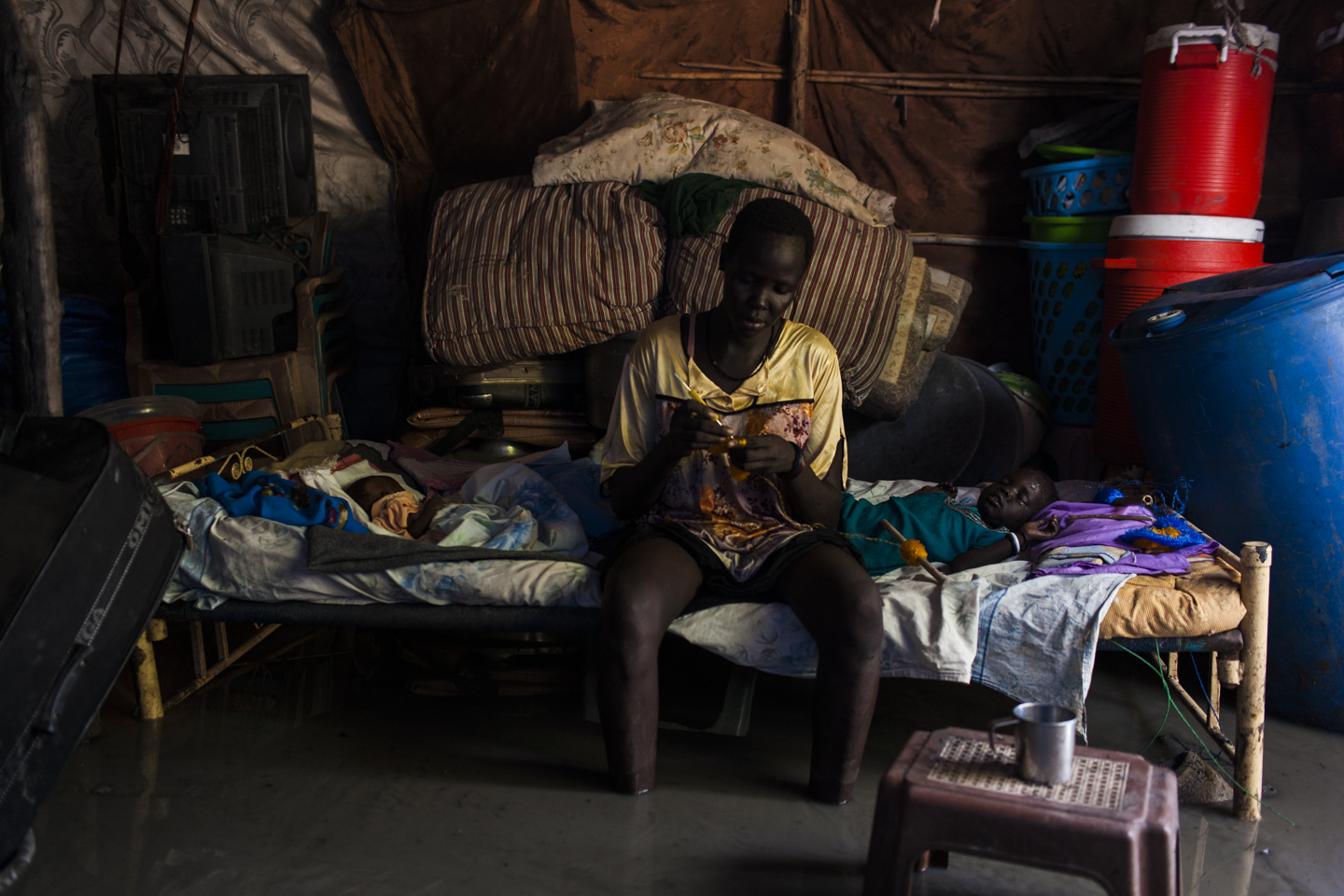 A mother sits with her two children in their flooded makeshift home at the UN base in Malakal, South Sudan, June 18, 2014. Seven days earlier she gave birth to her baby on the same bed.