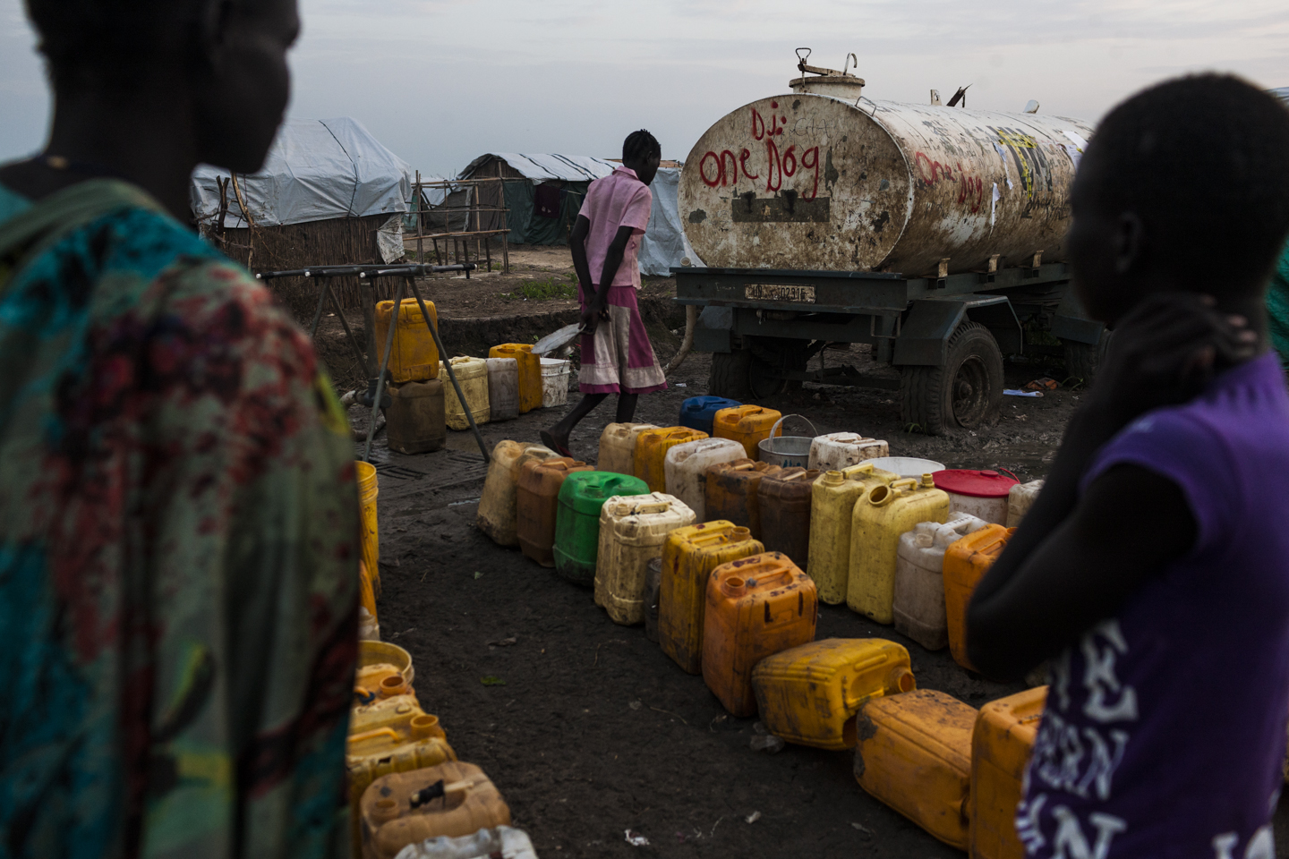 Women wait with their jerry cans for water to arrive by truck in the IDP camp in Bentiu, South Sudan, July 1, 2014.
