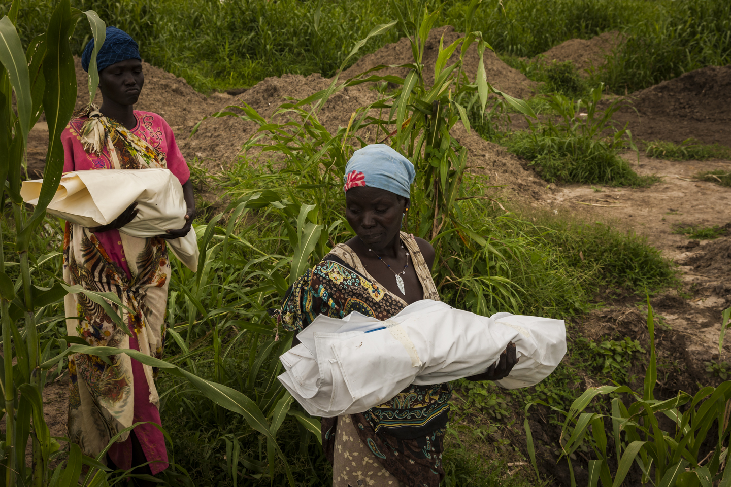 Martha carries the body of her 6-month-old daughter, while Veronica Nyachar follows her through the graveyard to burry her 1-year-old son Simon in the cemetery across the road from the UN base in Bentiu, South Sudan, June 30, 2014. The two bodies were placed in a mass grave with ten children.
