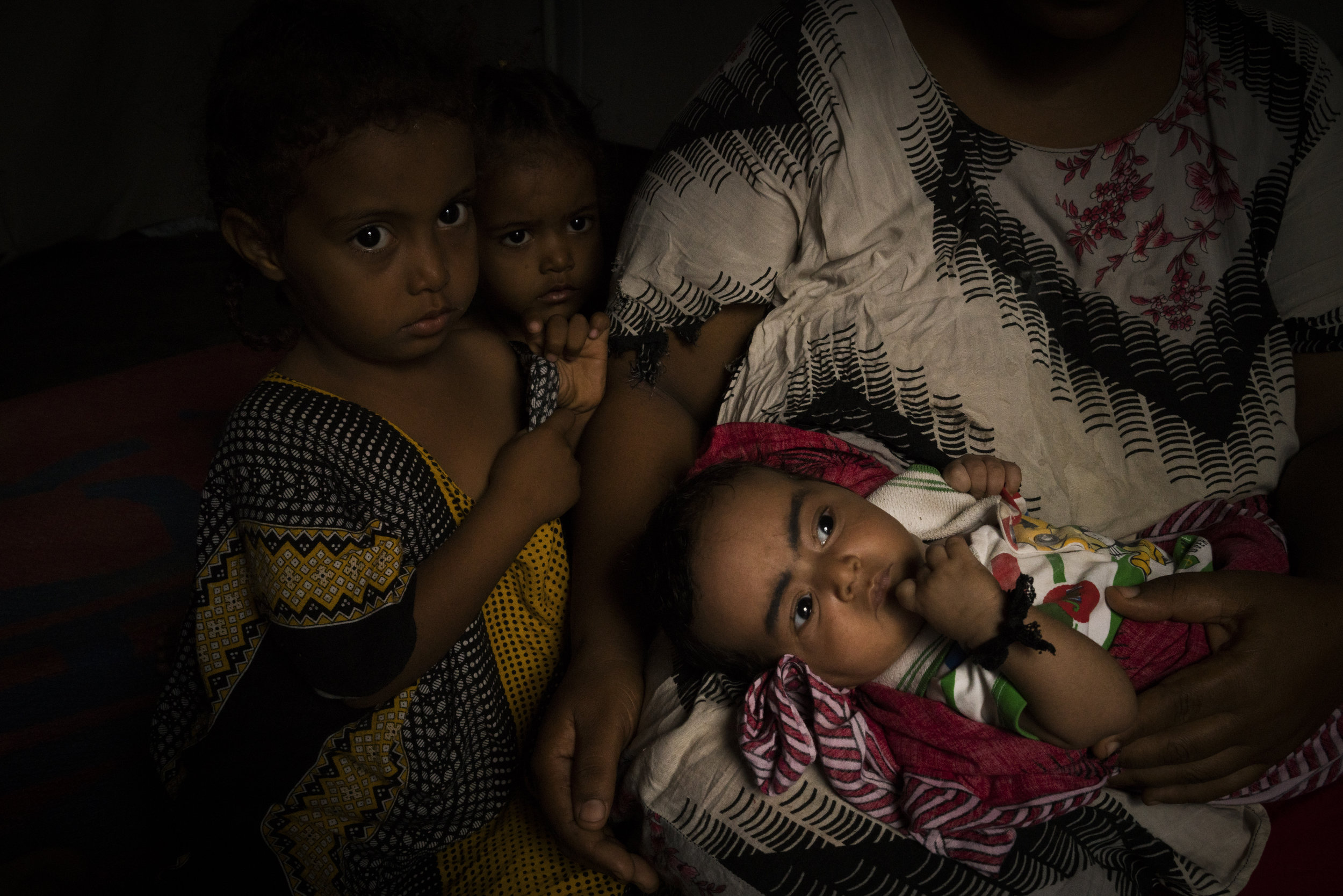 A mother who has fled the war in Yemen with her three children, comforts her baby who is sick and can not access medicine in the refugee camp in Obock, Djibouti, January 13, 2016.