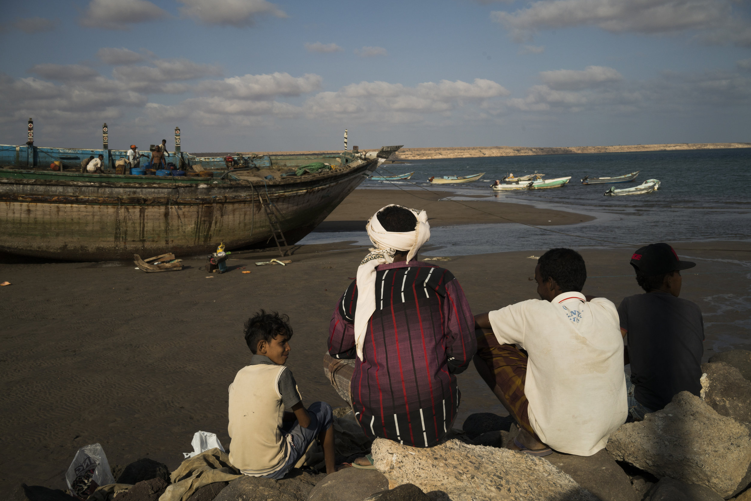Men watch as a boat is repaired in the port in Obock, Djibouti, January 12, 2016. Located just across the sea from Yemen Obock receives refugees fleeing the war, and at the time sends desperate migrants by boat in the opposite direction en route to Saudi Arabia.