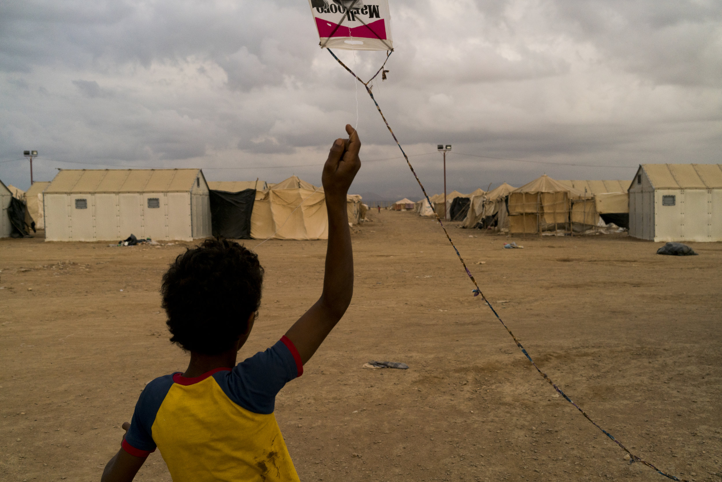A boy flies his homemade kite over the roofs of the tents that house over 3,000 Yemenis refugees who have fled to Obock, Djibouti, January 13, 2016.