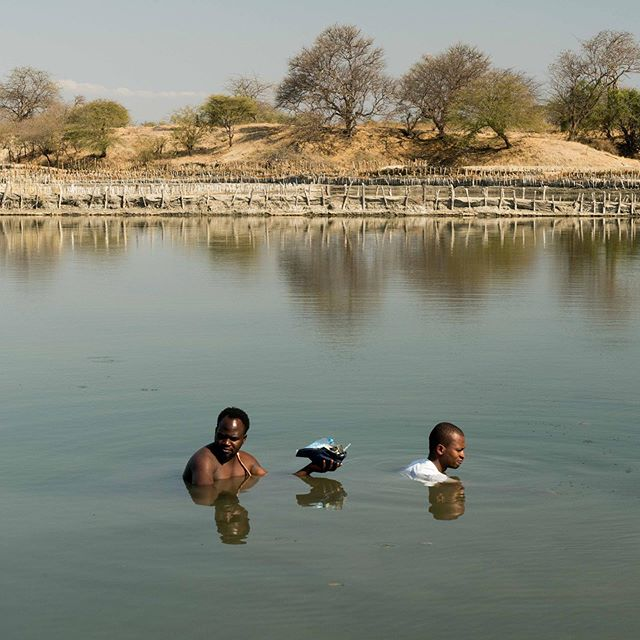 Graduate Geochemist Karim Mtili, age 26, (R) collects samples from the salt pond and places them in a hat with the help of Godfrey who is from the village of Itumbula, Tanzania, July 5, 2019.  On the hunt to photograph, locate, and extract helium - a colorless, odorless gas, that if not tightly contained escapes not only its container but also Earth's atmosphere. Some images of the process in southern Tanzania for @businessweek #earth #air #water #gas #elements #exploration #science #neverstopexploring #pond #Tanzania #Africa #helium #swim #swimming #photo #photograph #photography #photojournalism #adrianeohanesian