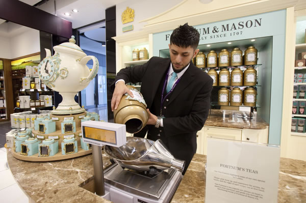 Tea being carefully weighed at Fortnum & Mason, established in 1707.