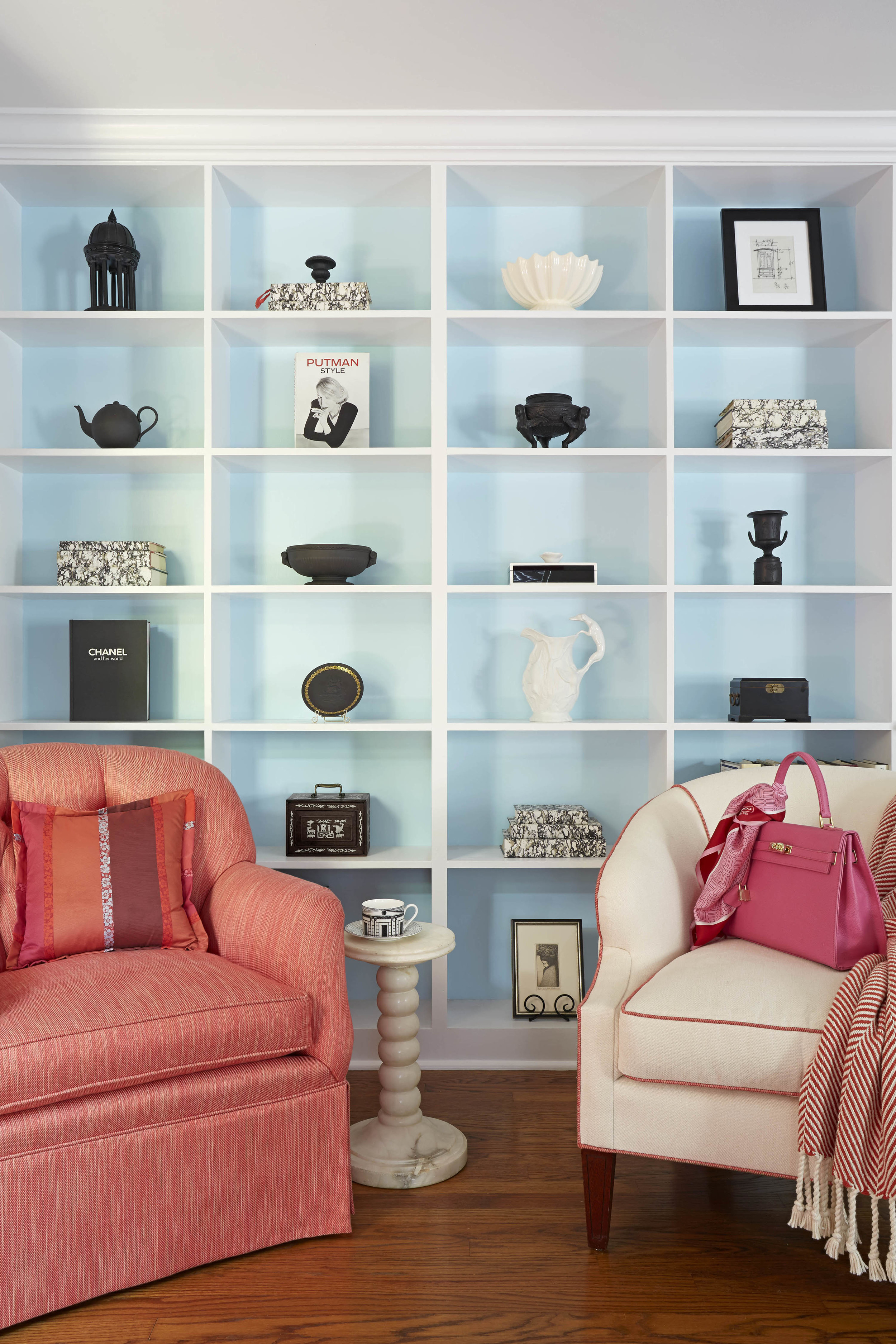 All the furniture used in this room was already in the space but was reimagined in fresh new fabrics. I loved the more sparse and edited arrangement within the bookcase. The background is Benjamin Moore Flower Blue, a vivid Robin's egg color that makes everyone feel a moment of joy. Colors can be very powerful. The hot pink Hermes Kelly bag was one of the inspirations for the room.