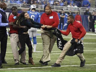 Araceli Rodriguez is dragged off the field by security.