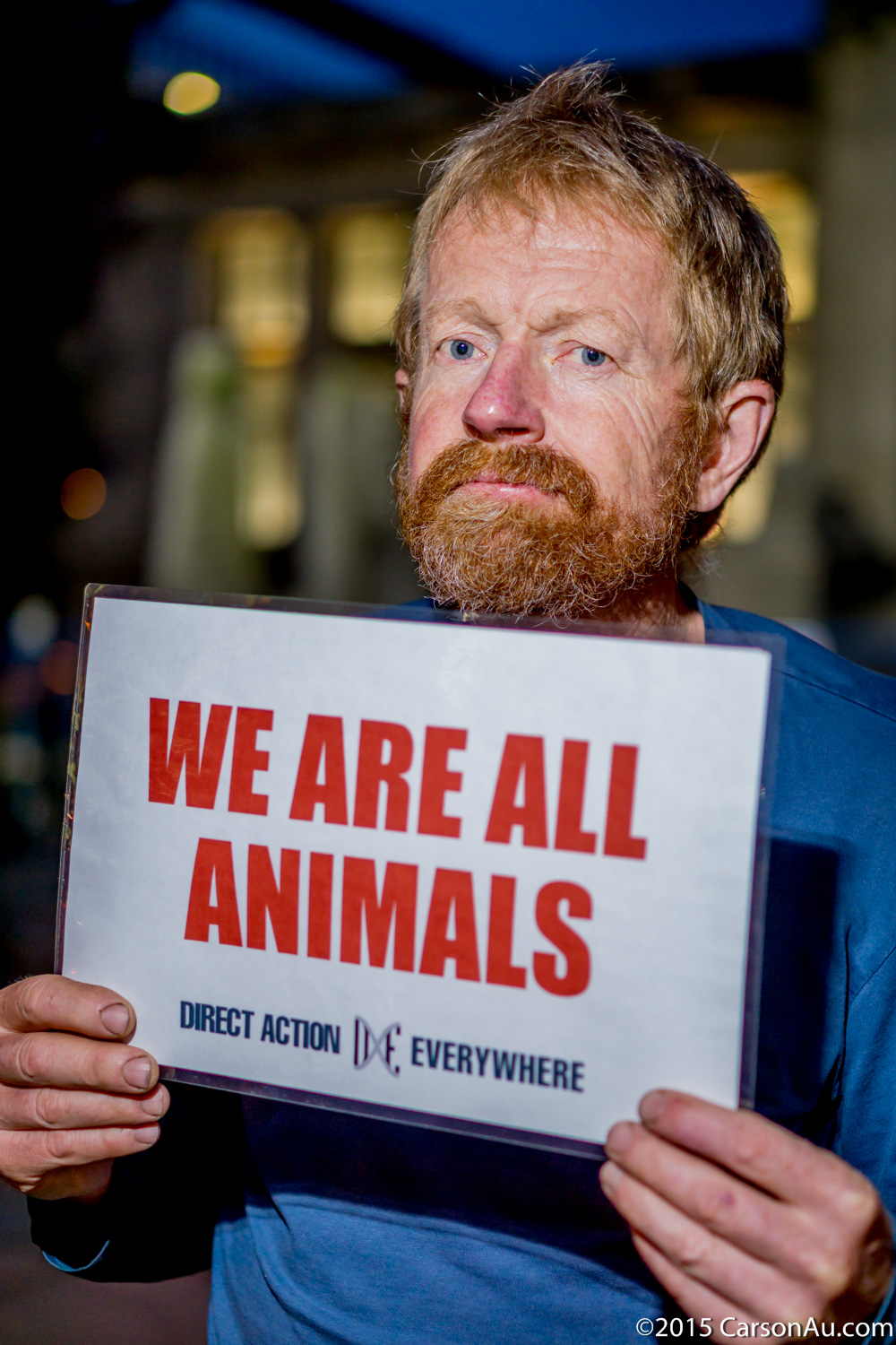 """Stephen, an activist from Vancouver, holds up a """"We Are All Animals"""" placard."""