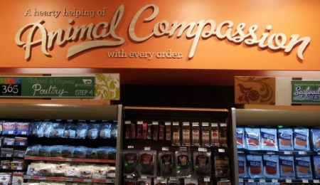 "A sign above a Whole Foods meat and seafood section claiming ""A hearty helping of Animal Compassion with every order."""