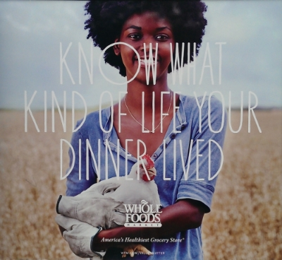 "An ad from Whole Foods' ""Values Matter"" campaign. Here, a human is holding a chicken lovingly with the strange caption ""Know what type of life your dinner lived."""