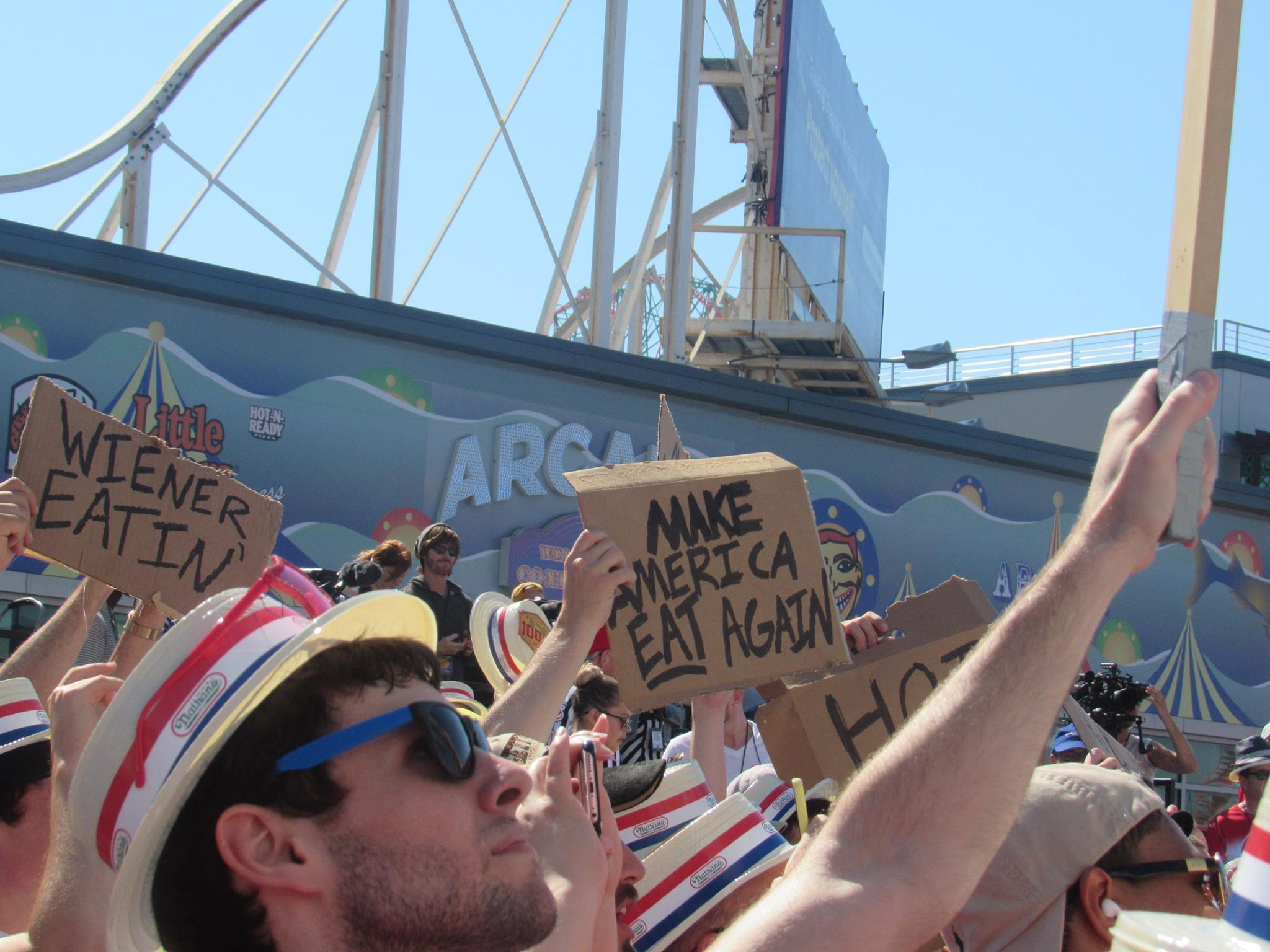 """An event-goer holds a sign that says """"MAKE AMERICA EAT AGAIN"""""""