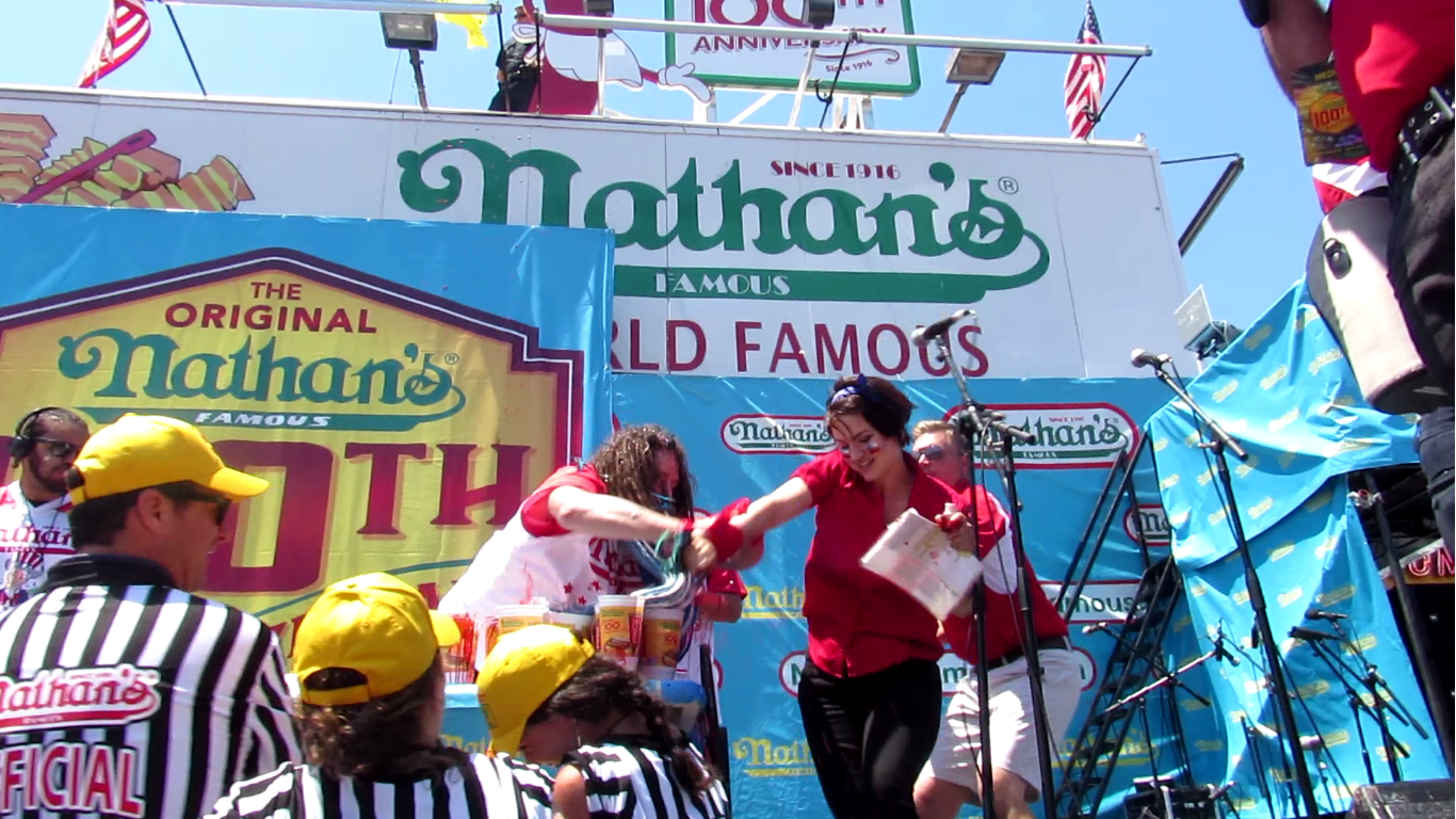 """Activist Rachel is grabbed by contestant """"Crazy Legs Conti"""" while squirting fake blood on the hotdogs."""