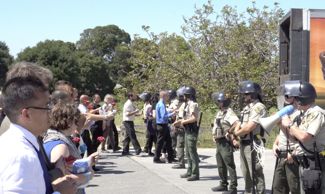 DxE protestors head towards police during a mass Open Rescue at an Amazon and Whole Foods egg farm in Petaluma. Photo by Direct Action Everywhere