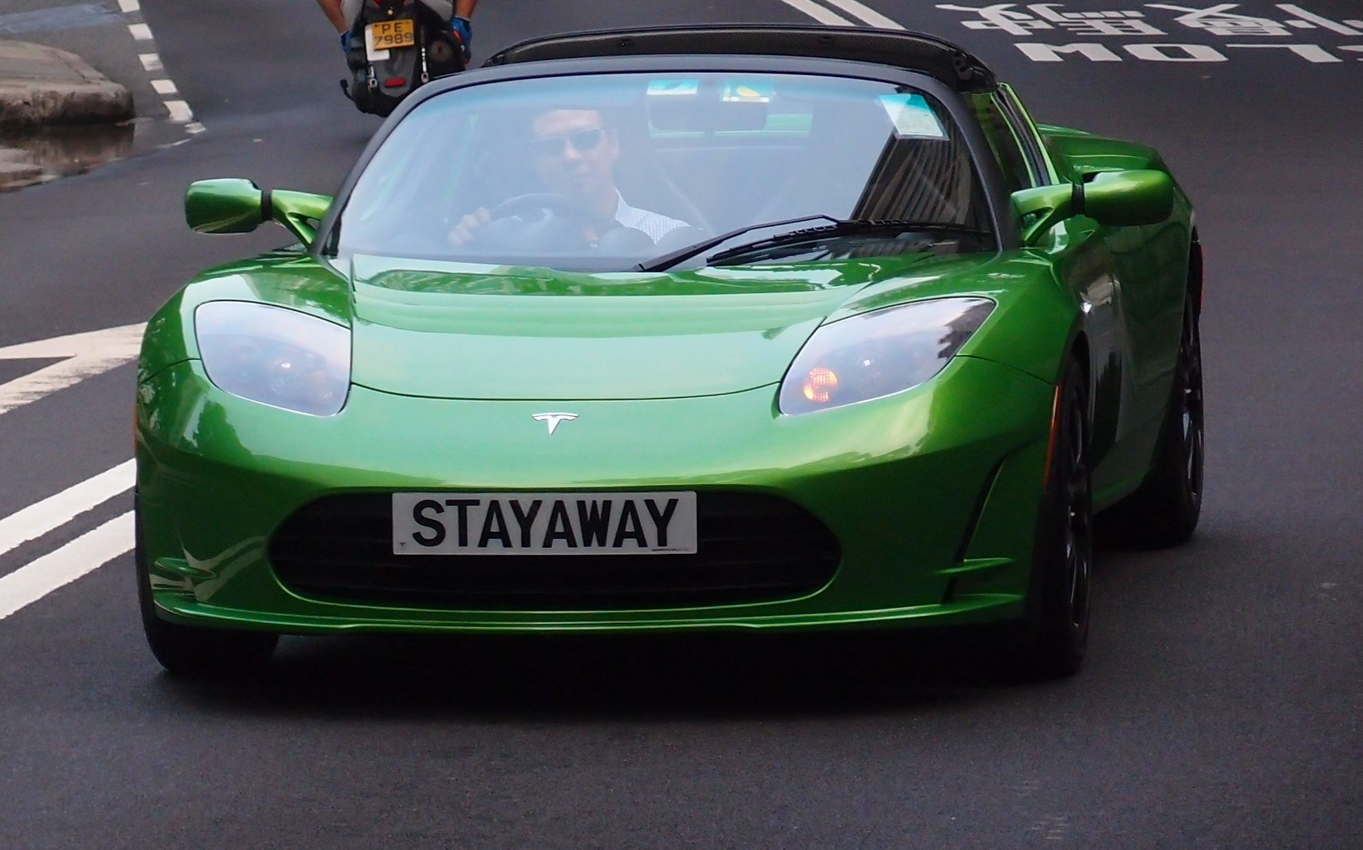 I hate plug in cars and I hate this little Tesla sport's car, the number plate is cool though