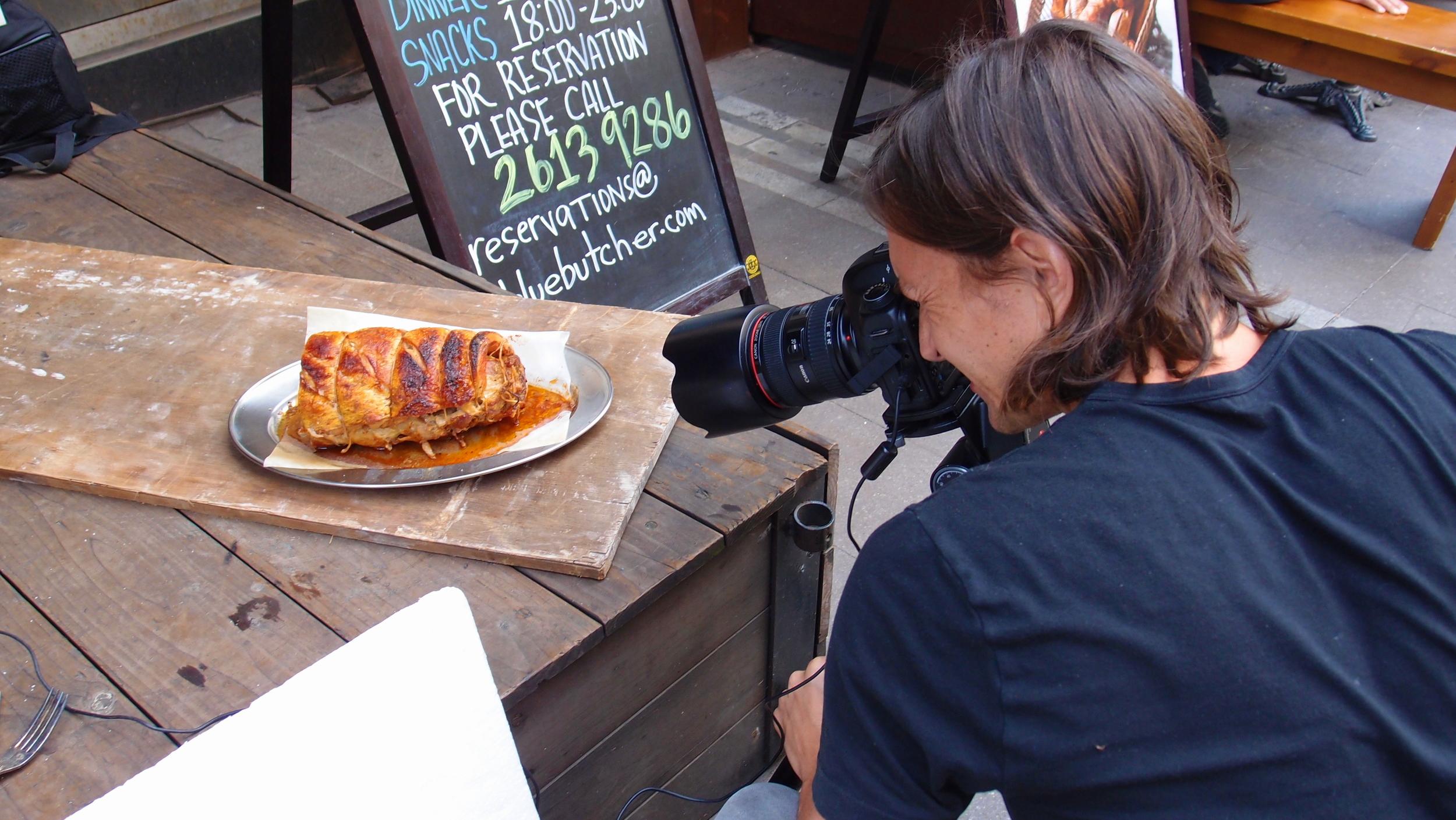 A random guy photographing a random piece of meat outside a random Italian Restaurant