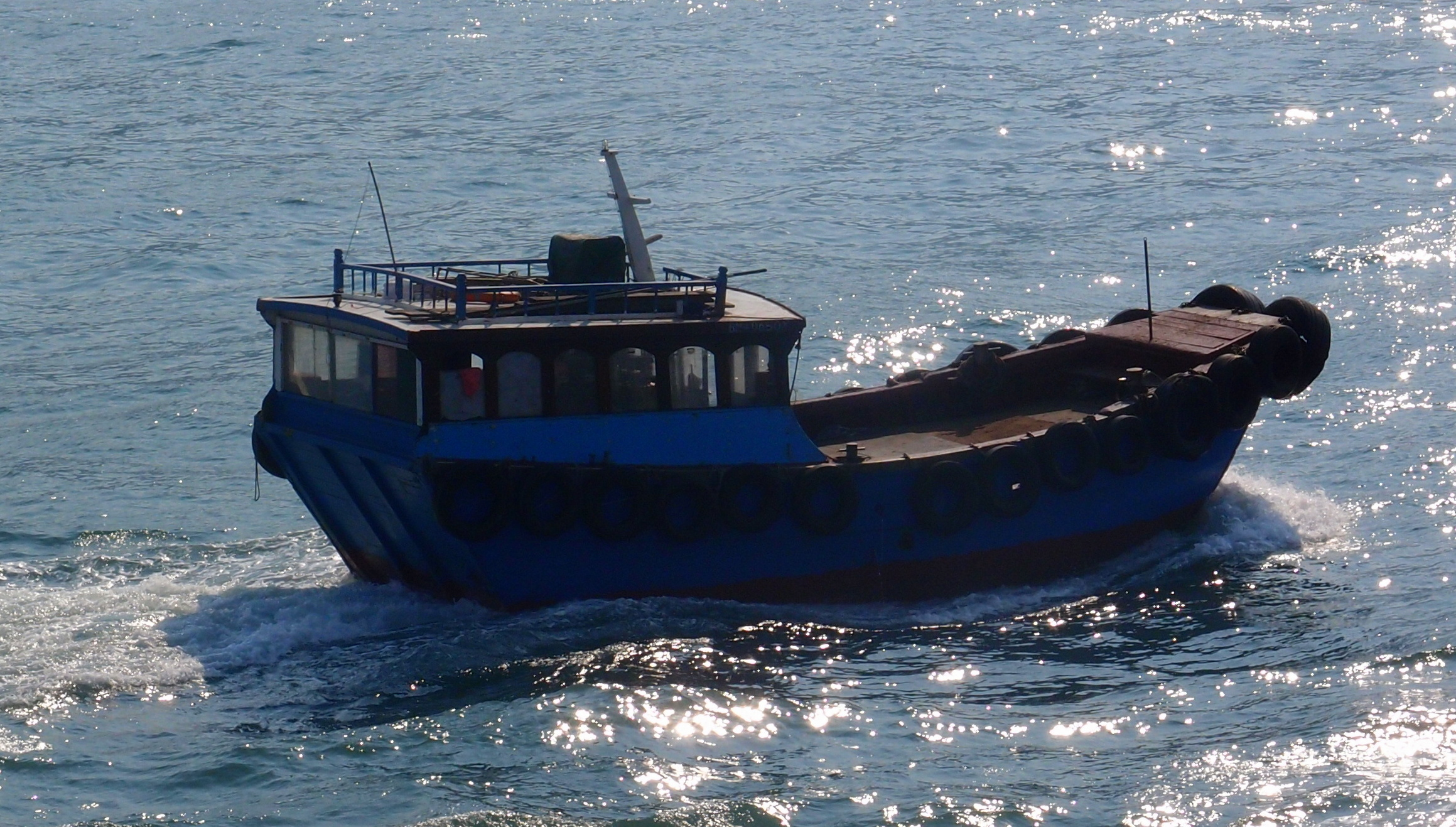 A small boat bobbing around in Hong Kong harbour