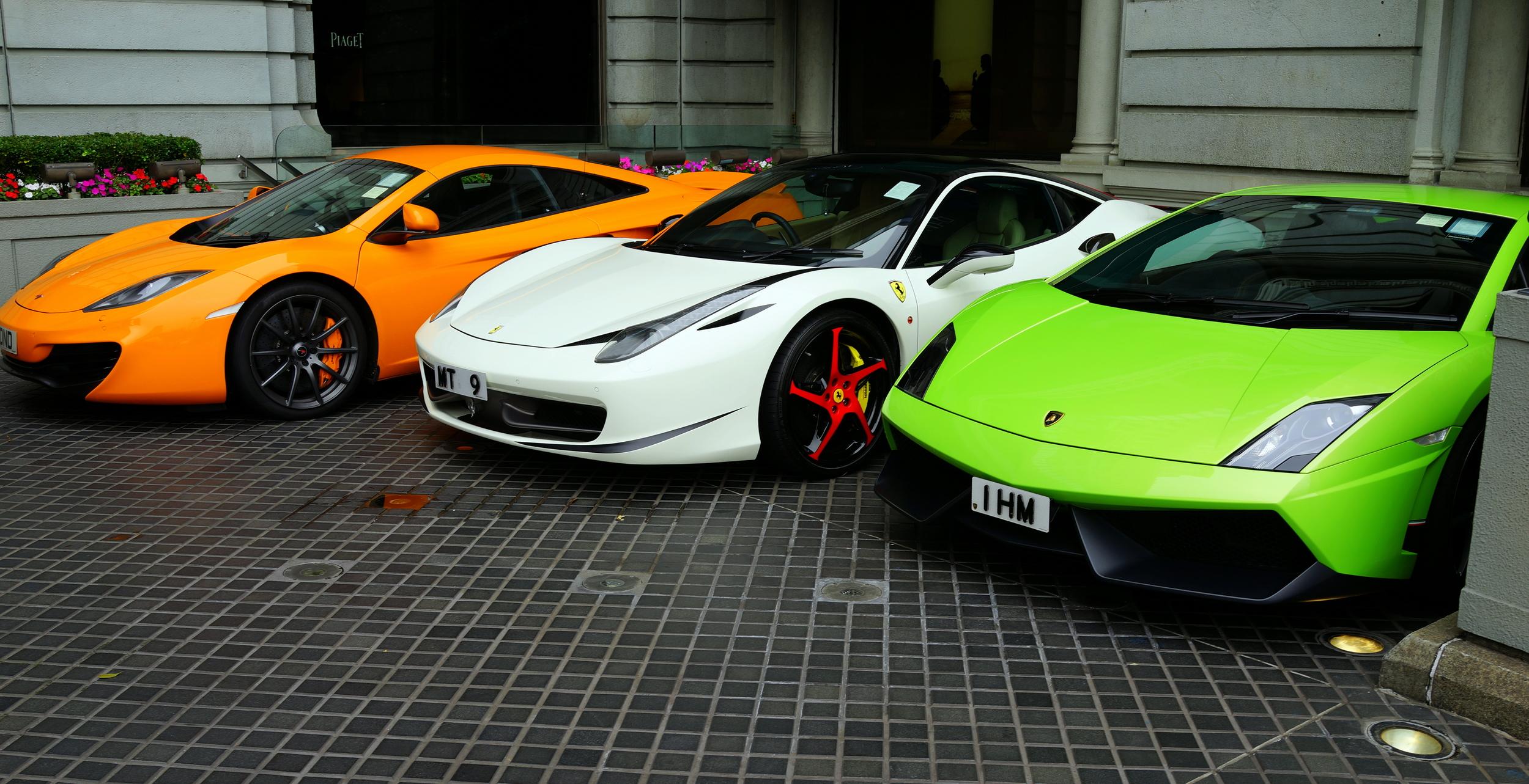 An orange McLaren, a white Ferrari and a green Lamborghini parked at the Peninsula Hotel
