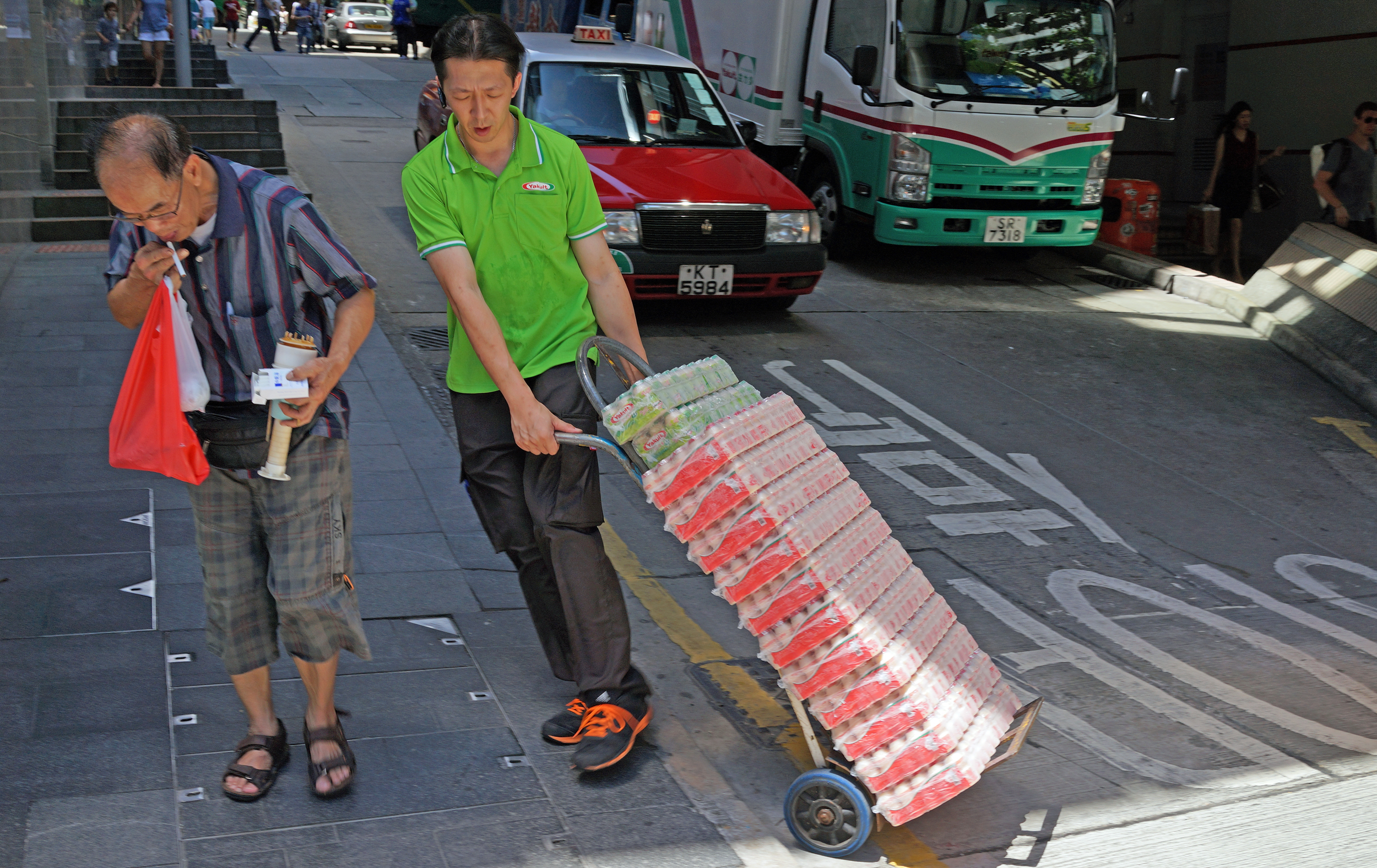 This delivery guy is delivering Yakult a highly addictive probiotic drink that I have been drinking for a very long time and it is also rumoured to have bust enhancing properties for young ladies which accounts for it's huge surge in popularity in Hong Kong.