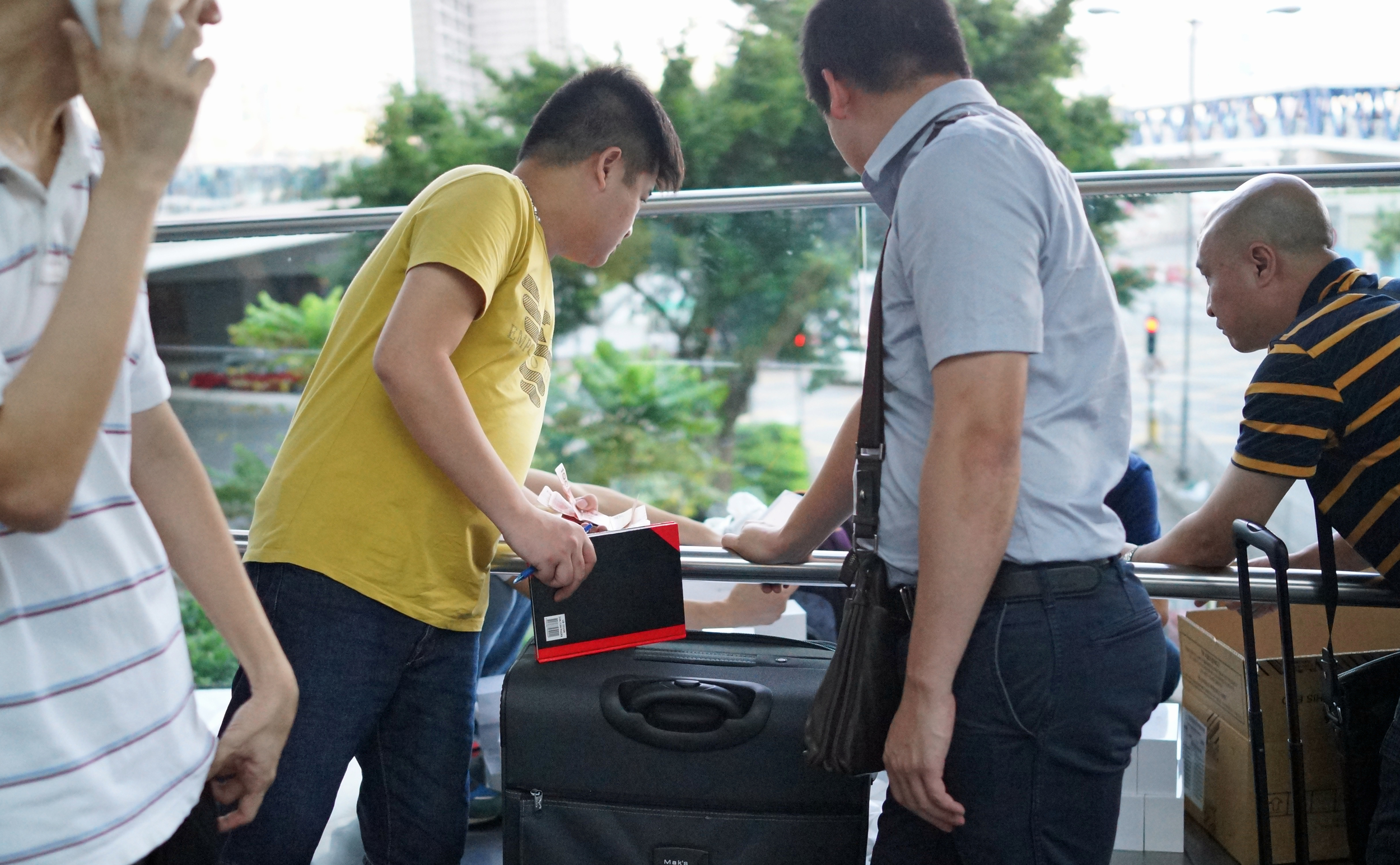 Mainland Chinese guys had suitcases full of the new phone, essentially they paid Hong Kong residents a large sum for their phone as soon as they came out of the store and then more than doubled the price and sold them to Mainland Chinese customers - all of this took place within 1 minute's walk of the Apple store!