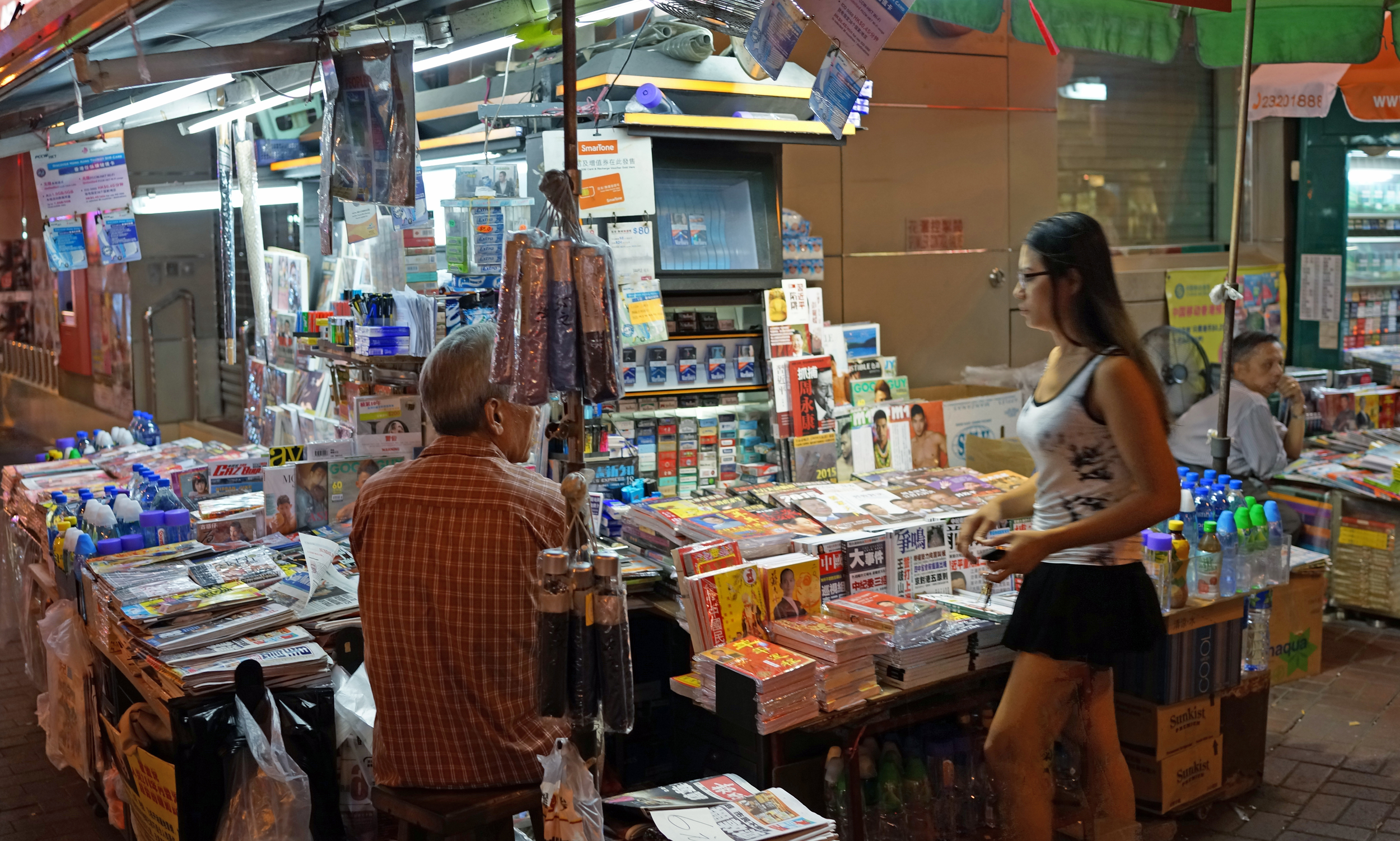 A typical newspaper stall - the old bloke is probably granddad and the young lady his grand daughter, they are sat there probably 350 days a year, 15 hours a day in all types of weather.