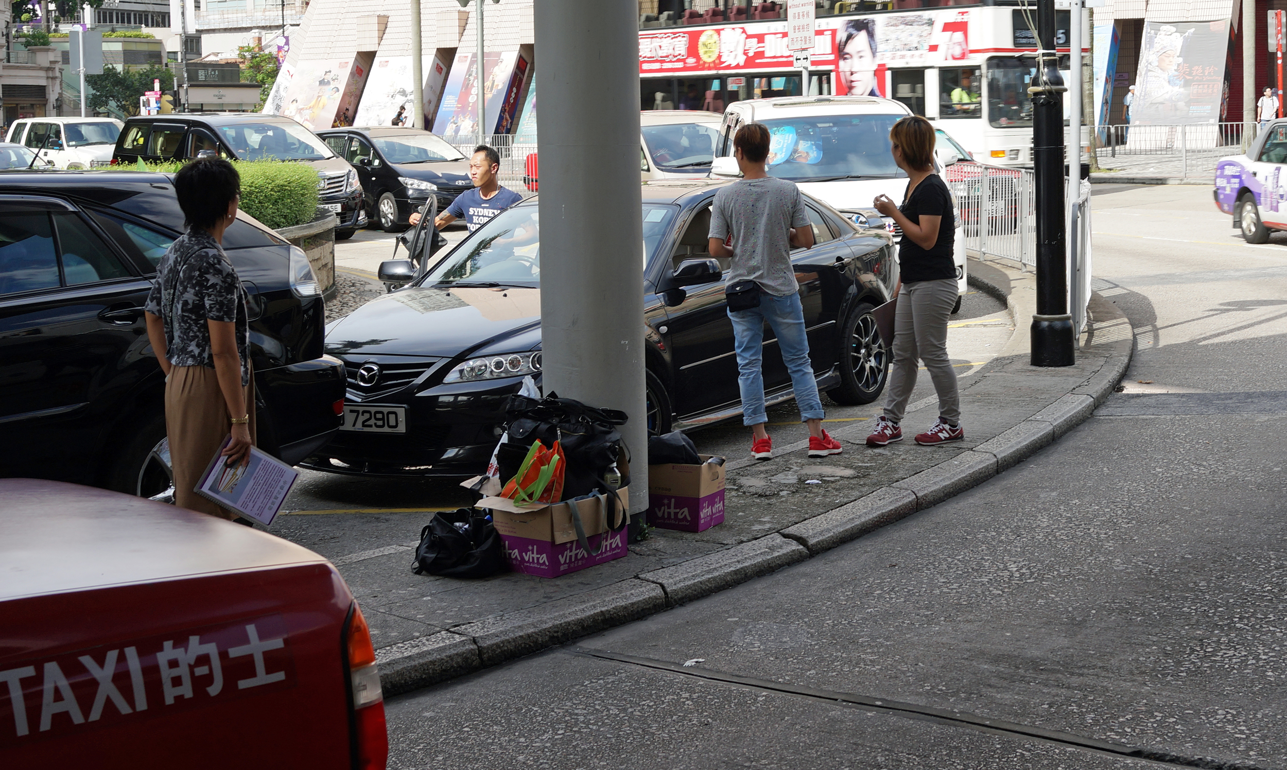 The guys and gals around the black Toyota are gang members, they control the seemingly hundreds of women who tout for business in and around the Star Ferry Kowloon and Canton Road - they offer berths on the gambling ships