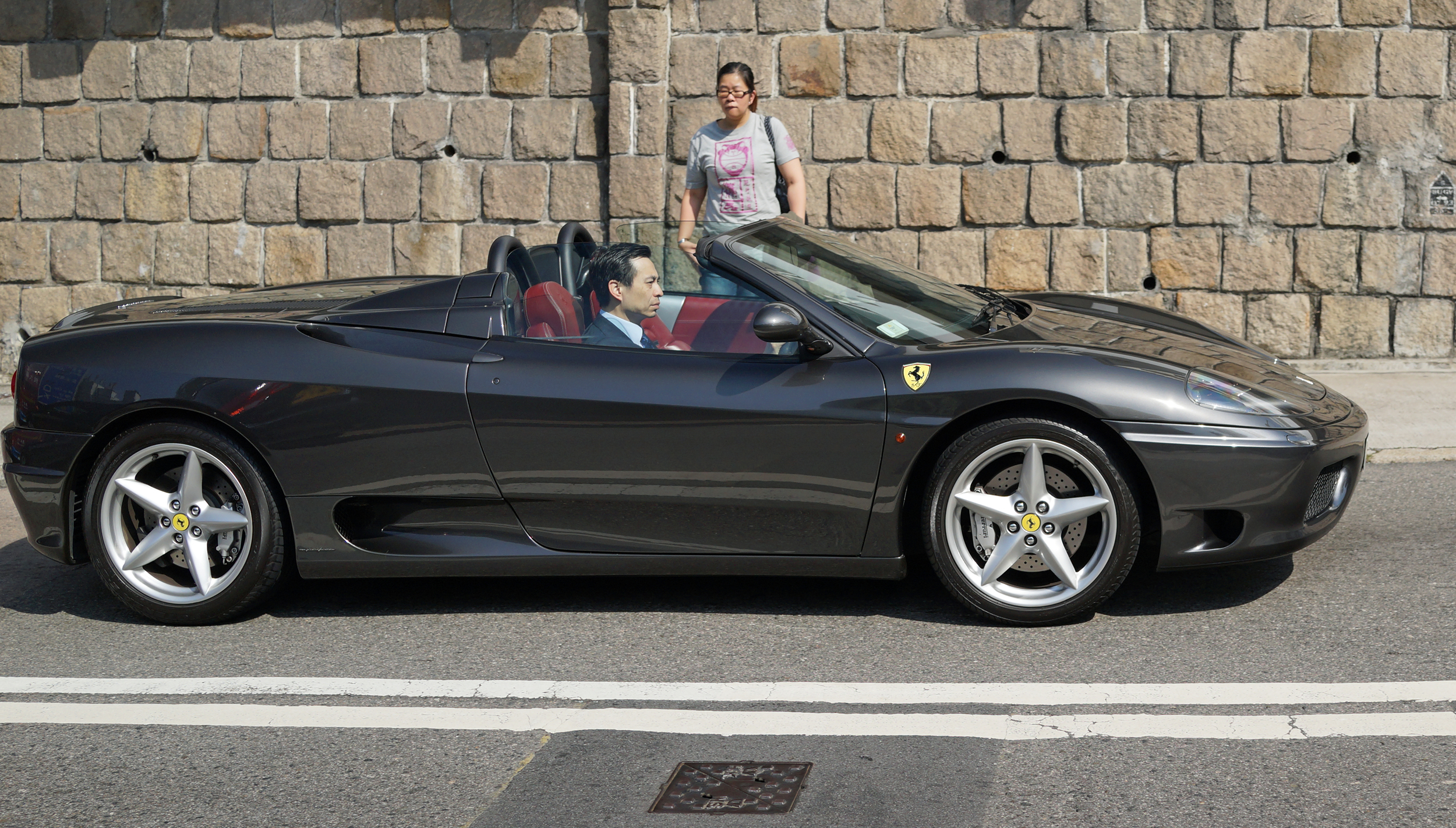 The guy in the suit in the Ferrari gets an admiring glance from a gobsmacked young lady near the Hong Kong Country Club.