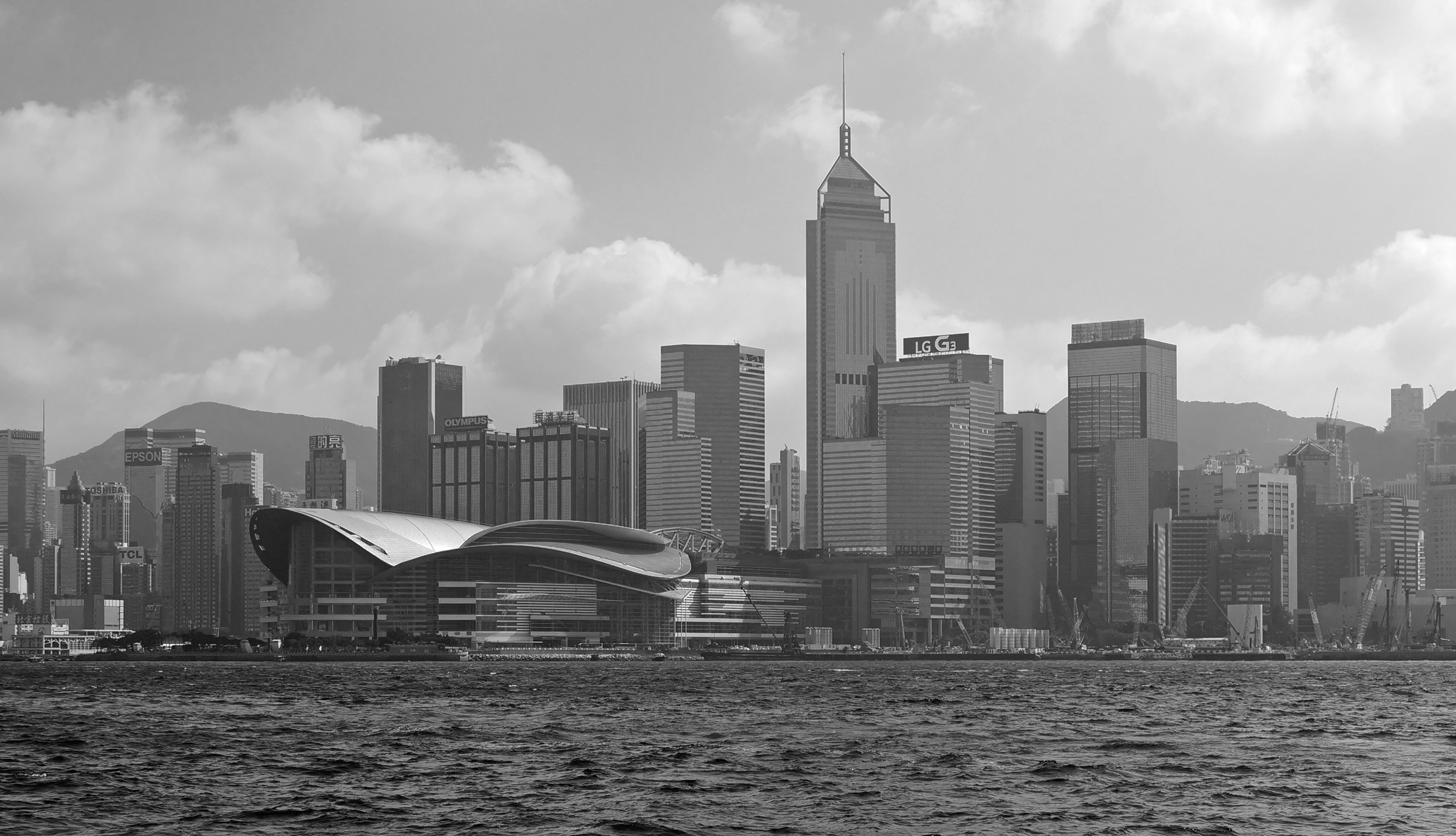 A black and white hazy view of the Convention Centre on Hong Kong Island -