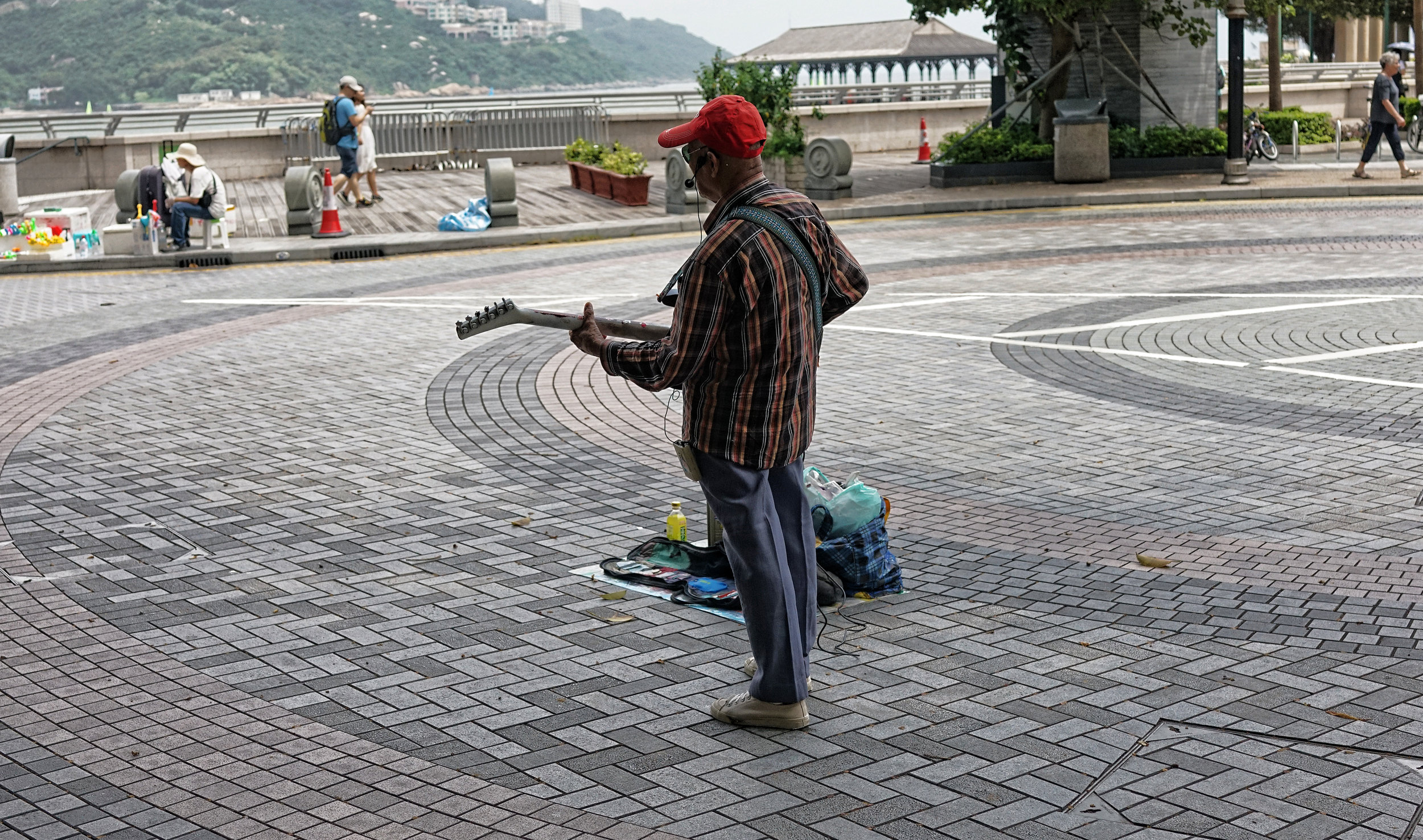 I could be kind and say that this crusty old codger is a legend in Hong Kong but he is not, I would cheerfully pay him to leave the area, he is   that bad  . He reminds me of Charlie Watts of the Rolling Stones who I am sure died and was stuffed about 20 years ago.  This chap has played at Stanley at the weekend for a long time and can be seen during the week on the bridge leading to the Star Ferry in Central alternating between cover versions of Elvis and the Shadows, in English.