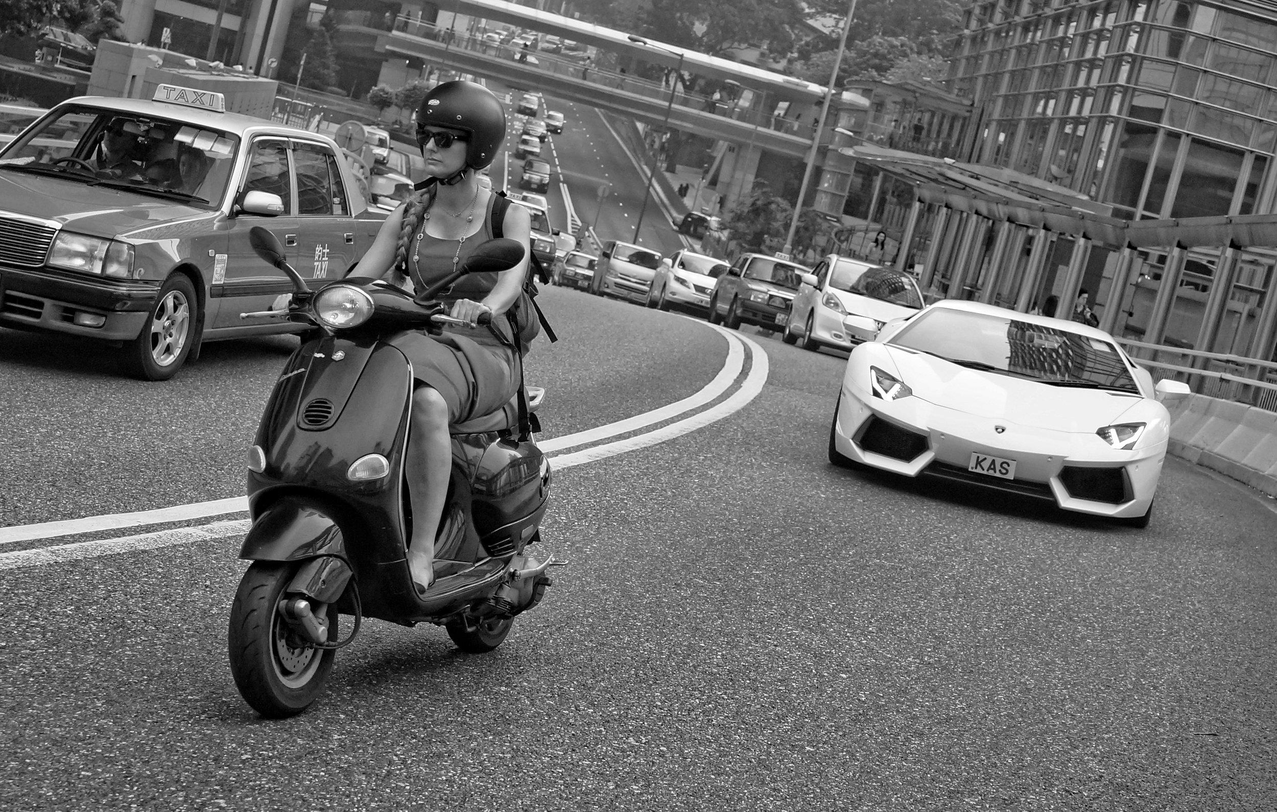 Lady on a scooter vs a chap in a Lamborghini, Garden Road, Hong Kong.jpg