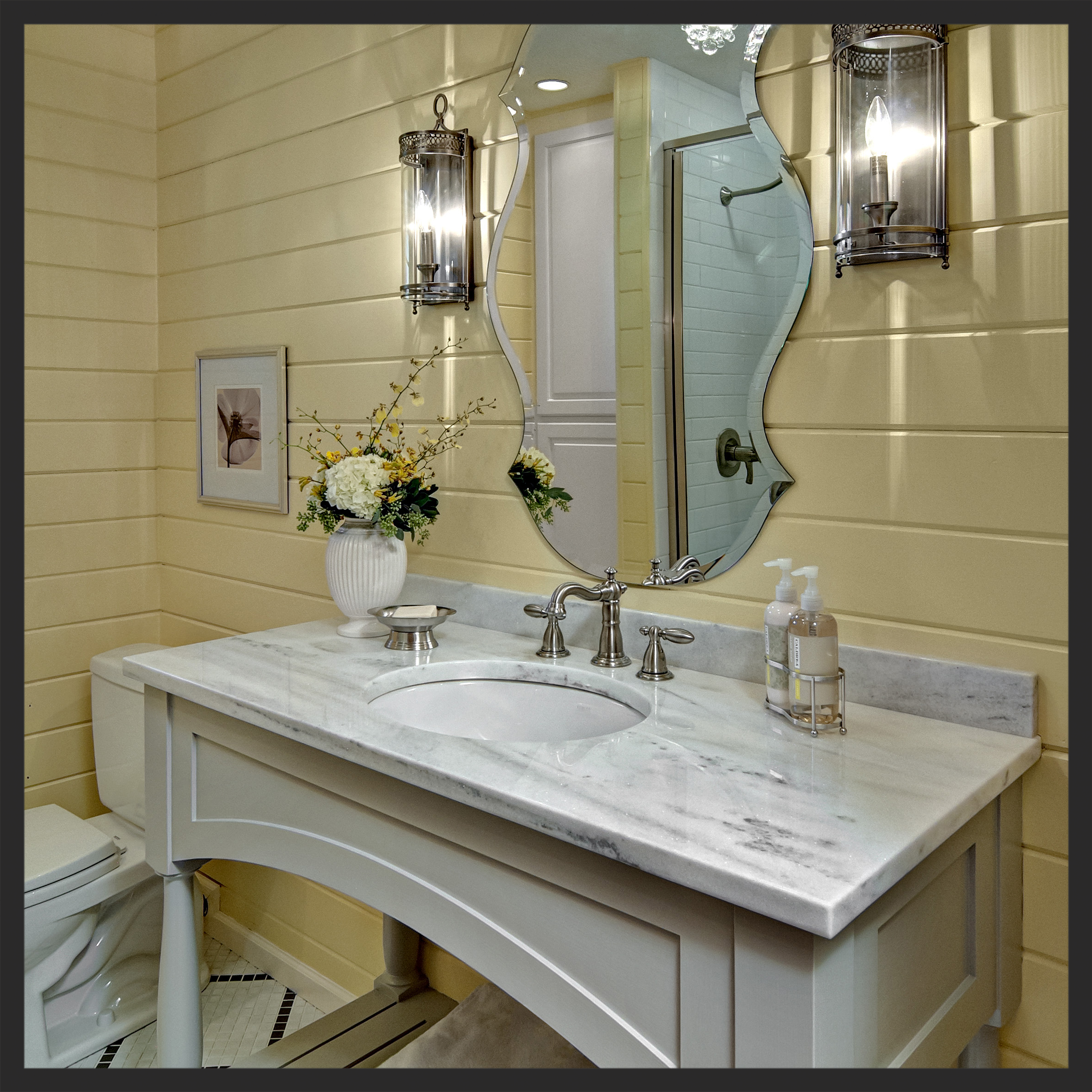This Cottage Chic Bathroom is a perfect fit for the yellow slat-boards, custom built cabinetry with Carrara marble top, rustic sconces and beveled mirror to swoon for.