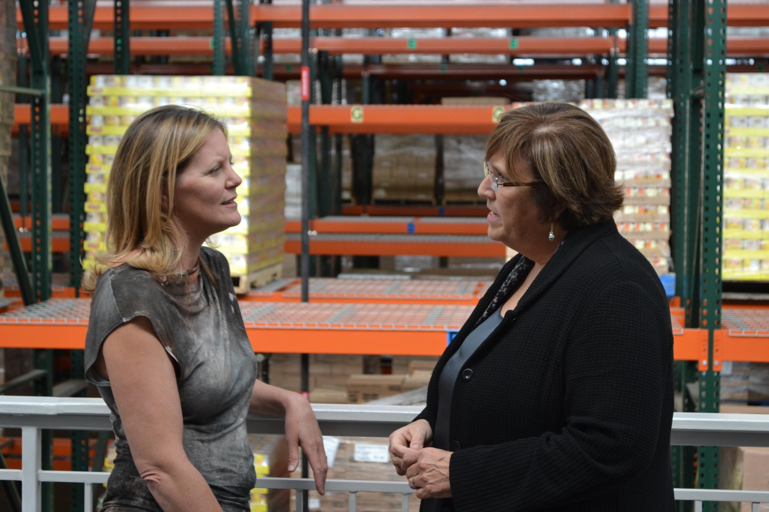 Heidi Legg speaks to Catherine D'Amato, President of The Greater Boston Food Bank inside the 21st century facility