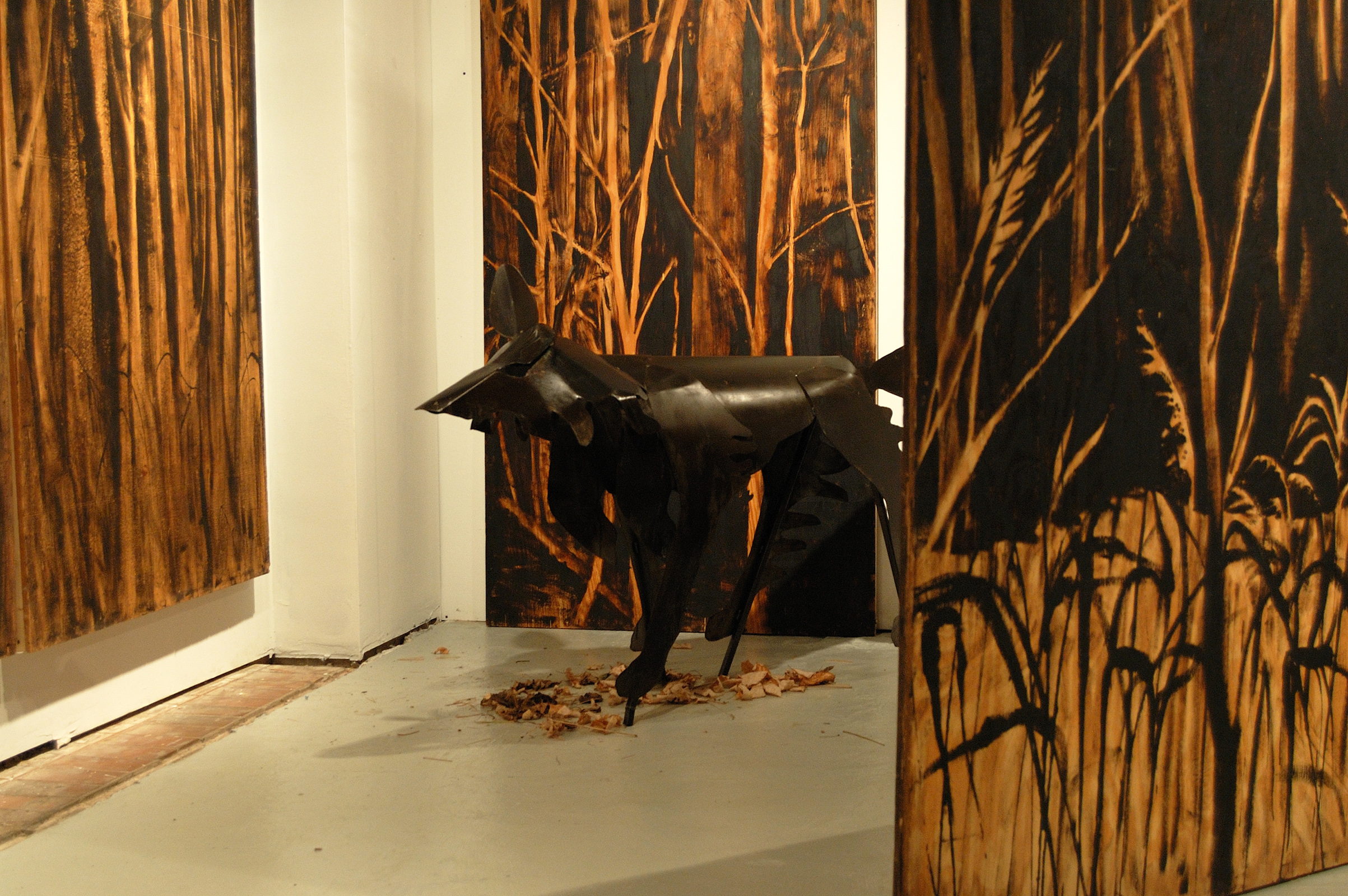 """Living Room"" was a one-person show at Gallery 13, 811 LaSalle St., Minneapolis, MN.  The animals are life-size, Corten steel, the panels, both freestanding  and wall-hung, are each 4' x 8' plywood, painted in asphaltum. The wolf here is called ""Grimm's Wolf"" and depicts human view of wolf as predator: the Big Bad one."