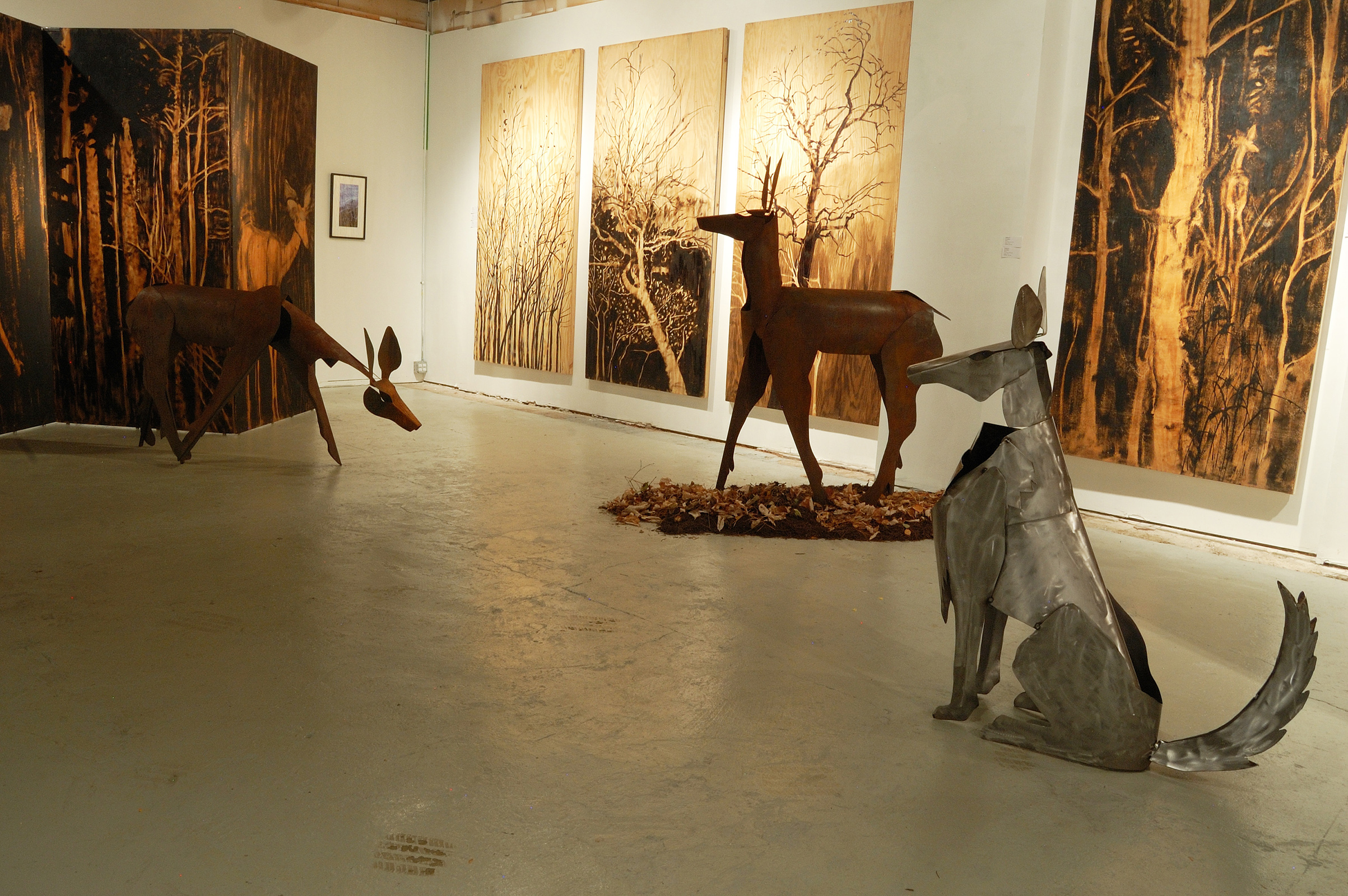"""Living Room"" was a one-person show at Gallery 13, 811 LaSalle St., Minneapolis, MN.  The animals are life-size, Corten steel, the panels, both freestanding  and wall-hung, are each 4' x 8' plywood, painted in asphaltum. Here is the other wolf, seated, keeping an eye on the deer."